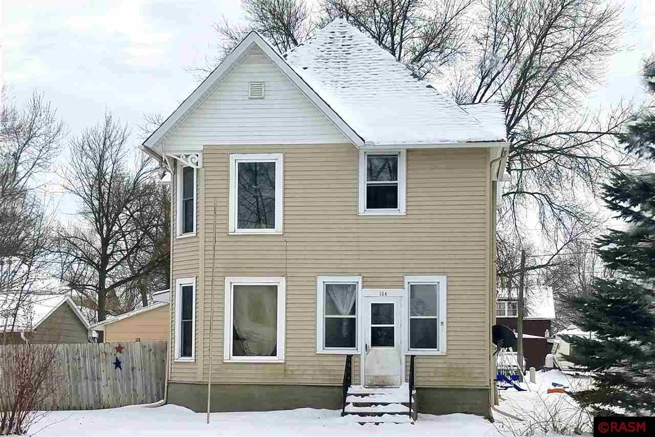 Grand 2 story home in the heart of Winnebago with 4 BR, 2 Bath, generous living and dining room area, bright and airy kitchen, large bedroom on the main level with two closets, and 3/4 bath with laundry area.  Main level is complete by a foyer with open staircase to the upper level and a 3 season front porch.  The upper level is comprised of 3 bedrooms and a 3/4 bathroom complete with a claw foot tub.  The walk-up attic can be accessed from a door on the second level, and there is room for future finished square footage up there as well!  100 Amp electrical service, vinyl siding, vinyl windows, 'On Demand' water heater, large deck outside kitchen door, and an attached 2 stall garage with alley access.  So much potential and square footage in this one!  Come take a look today!