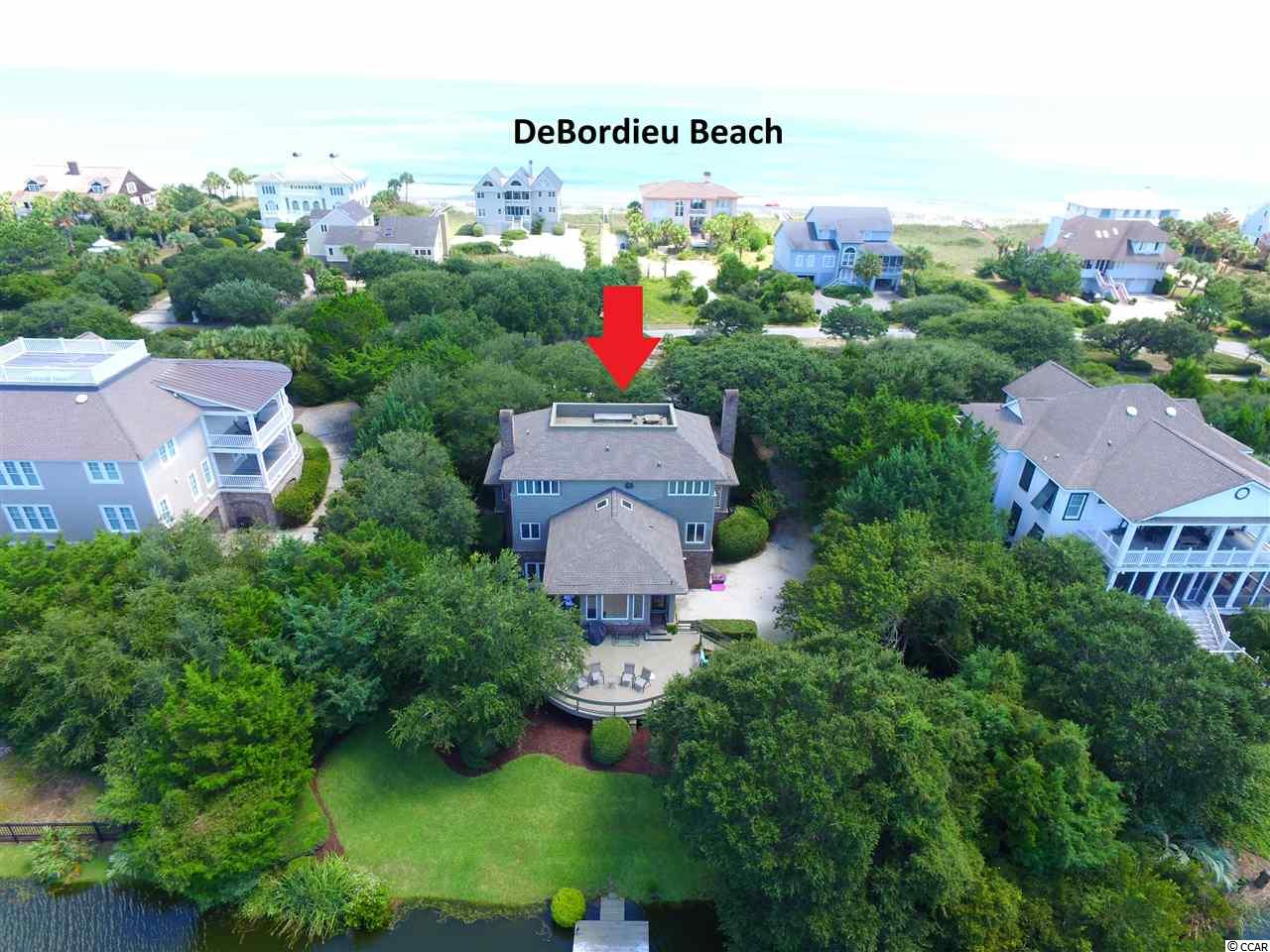 "Second row beach home in prestigious DeBordieu Colony directly across from a beach access. This nearly 4000 heated square foot home is surrounded by majestic live oak trees and has a dock with beautiful lake views! Enjoy fishing, paddle boarding or kayaking from your backyard while just steps across the street to spend the day at the beach. This remarkable house has been kept in impeccable condition. The kitchen has been renovated and has stainless steel appliances including a double oven and granite countertops. Two separate living rooms! One larger room with a fireplace for family gatherings and a smaller living room with custom wood paneling and built ins for a warm and charming setting. The back has a large deck with beautiful lake views. Downstairs is a garage converted to a ""game/activity room"" for entertaining! Huge master suite with a deck looking out to views of the Atlantic Ocean. Rooftop deck with gorgeous ocean and DeBordieu community views! DeBordieu Colony is a gated, beachfront community located between Georgetown and Pawleys Island. Residents enjoy riding their golf carts to the beach or put their boat in at the community boat dock for a day in North Inlet. Community residents are eligible to join the DeBordieu Club. The club offers world-class golf, tennis, onsite dining, tiki bar, access to oceanside pools, fitness center and many other social activities! DeBordieu is just a 60 mile drive to historic Charleston, SC or a 35 mile drive to the attractions of Myrtle Beach. This community is one of a kind. Don't miss this opportunity to live like you are on vacation!"
