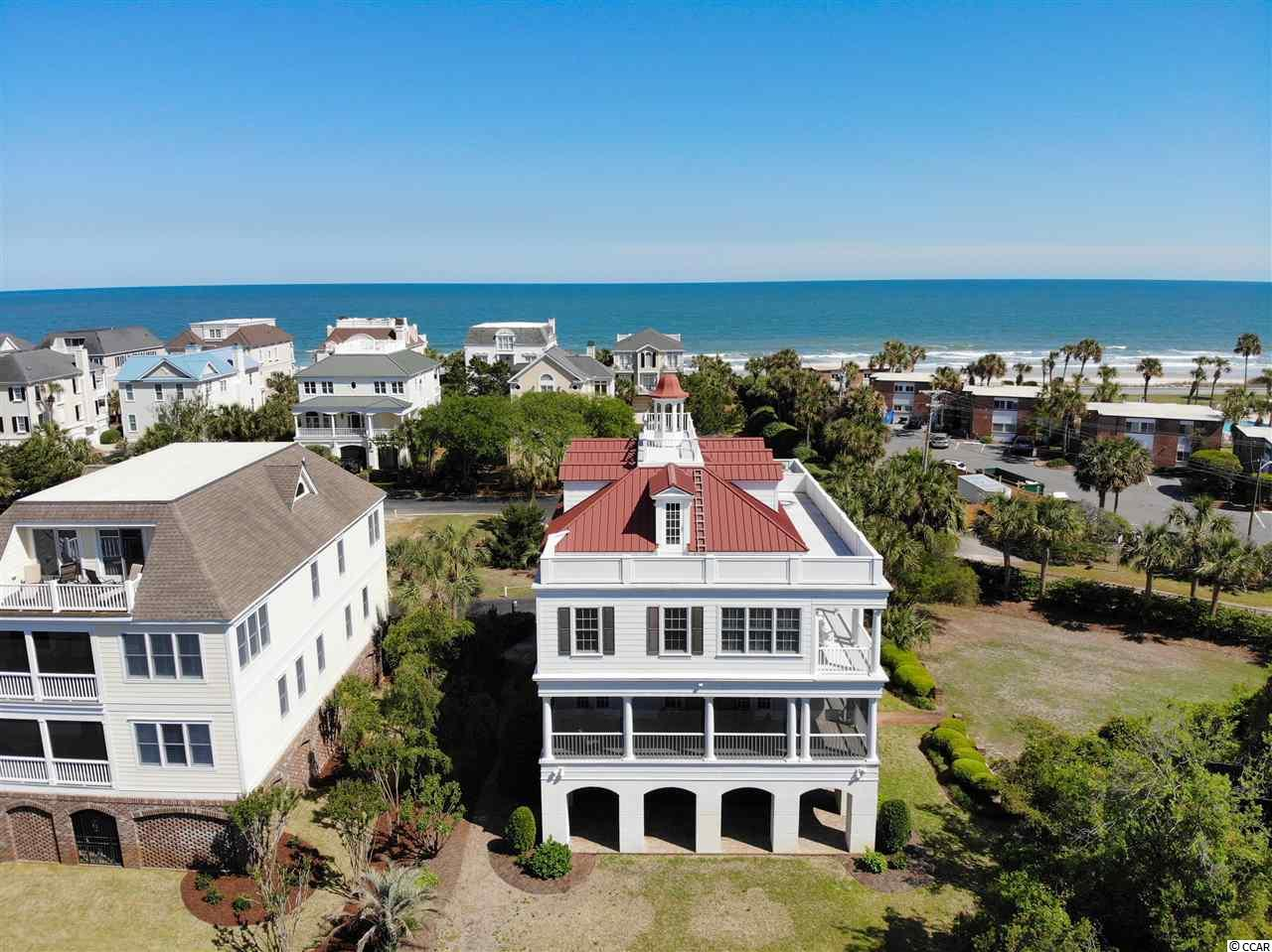 """Beautiful marshfront home in Charlestowne Grant in prestigious Litchfield by the Sea.  Just steps to the beach! Enjoy ocean views from the front and marsh views from the back!  The best of both worlds!  This well-built home has gracious sized rooms.  Enjoy sitting in the living room with expansive views of the marsh or walk on the large outdoor screen porch to enjoy the evening sunset.  Upstairs is a large deck and rooftop balcony to feel the ocean breeze, enjoy views of Litchfield by the Sea and South Litchfield and look out over the marsh.  The meticulously kept house has hardwood floors, crown molding, elevator, granite countertops, many built-ins, central vaccuum, water filtration system, metal roof and plenty of living space.  There are two fireplaces, one in the living room and another in the """"keeping"""" room off of the kitchen.  The master suite has an adjoining sitting room with porch access.  This house has so much to offer.  Don't miss this chance to enjoy beach living.  Litchfield by the Sea is a gated community with private beach access, lighted tennis courts, beach clubhouse, pool, fishing and crabbing piers and more.  Just a 70 mile drive for a day trip to Charleston, SC or a 35 mile drive to the attractions of Myrtle Beach."""
