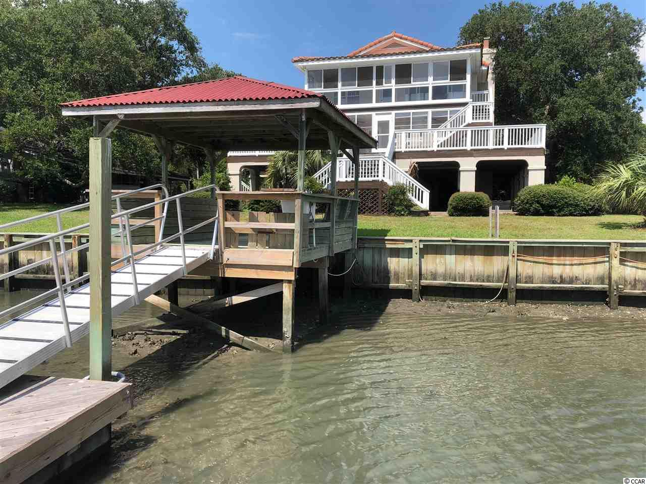 Great creek front home on very private double lot with spectacular inlet views! Property is within walking distance to many local attractions including the Murrells Inlet Marsh Walk and the bike path to Brookgreen Gardens and Huntington Beach State Park. Floor plan features over 3,000 heated square feet of living space complete with 5 bedrooms, 4 full baths, 2 half baths, 2 sun rooms, a wood burning fireplace on each level, and a large outdoor entertaining area with separate kitchen and bath. Nearly every room has porch access and a view of the inlet! Third level is separate from 2nd level and can be used as a mother-in-law-suite, guest quarters, or can be combined with main living area. An additional bedroom/office and full bath with private entrance is located on the ground level. 4 bay carport, multiple storage areas, and large dock ensure enough space for all of your toys! Deep water access during appropriate tides. Unobstructed views of Murrells Inlet, Huntington Beach State Park, jetties, and the Atlantic Ocean. Home needs a lot of TLC, but the possibilities are endless with this unique property! . All information is deemed reliable but should be verified by all potential buyers and agents.