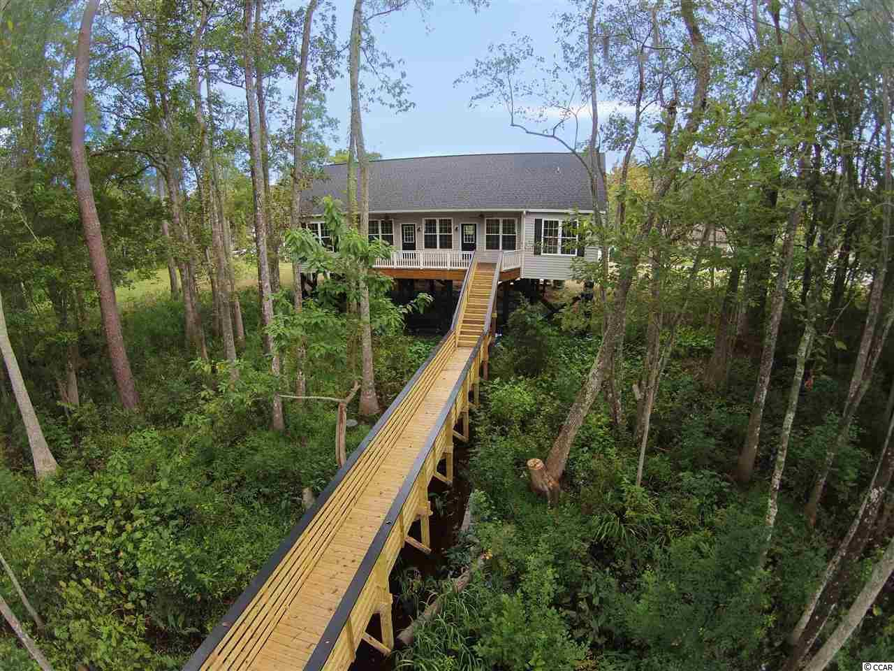 3bed/2ba house Right ON the Intracoastal Waterway and NO HOA!  Granite countertops and hardwood floors! Ceiling fans in every room. Large open floor plan. Oversized deck stretches across the entire back of this house so you are part of nature and water from almost every room in the house.  Walk down the walkway lined by beautiful trees and natural landscaping to the new pierhead to your docked boat or just watch the boats go by. LOTS of parking including a detached carport which also includes a storage room. This is a nature-lovers dream house but convenient to everything Myrtle Beach has to offer including Coastal Grande Mall, Tanger Outlets, marinas, public docks, landings, restaurants, golf courses, shops, entertainment, Myrtle Beach International Airport, Broadway At The Beach, The Market Common, Barefoot Resort and Coastal Carolina Univeristy (CCU).  Perfect for a primary or 2nd home. The Waterfront is a secluded 5-lot subdivision directly on the Intercoastal Waterway. Adjacent Lot (to the left of the house) is also available for sale! MLS 1804913.