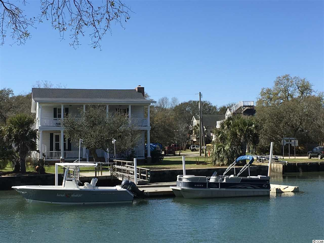 You Will Immediately Fall In Love With This Creek Front Home. Unique Beach Home with 103' of Direct Channel Access. This Home Radiates History and Fond Family Memories. Privately Owned BOAT RAMP. Not to mention a Stationary Dock - 16 x 14, 2 Floating Docks - 48' x 8' and the 2nd Dock - 16' x 10' with a Walkway 16' x 3'- AND a Concrete Sea Wall. Plenty of Room to Dock Several Boats. The Yard is a Great Size for Children Playing or Family Games and Barbecues. The Stationary Dock is set up with a Utility Sink to Clean Those Freshly Caught Fish as well as a Built in Bench. Interior Completed with Reclaimed Wood from a Church and a Railroad Station in Marion. 7 Bedrooms Total and 4 Baths, 2 Laundry Rooms and 2 Family/ Bonus Areas. Great Place to Gather the Entire Family for Memorable Summer Parties and All Year Round Gatherings. DIRECTLY on the INLET and Five Minutes Away From Restaurants,Entertainment and The Inlet Marsh Walk. Amazing Views of the Inlet from Both 34' Porches and a Wonderful Balmy Breeze Off the Inlet.