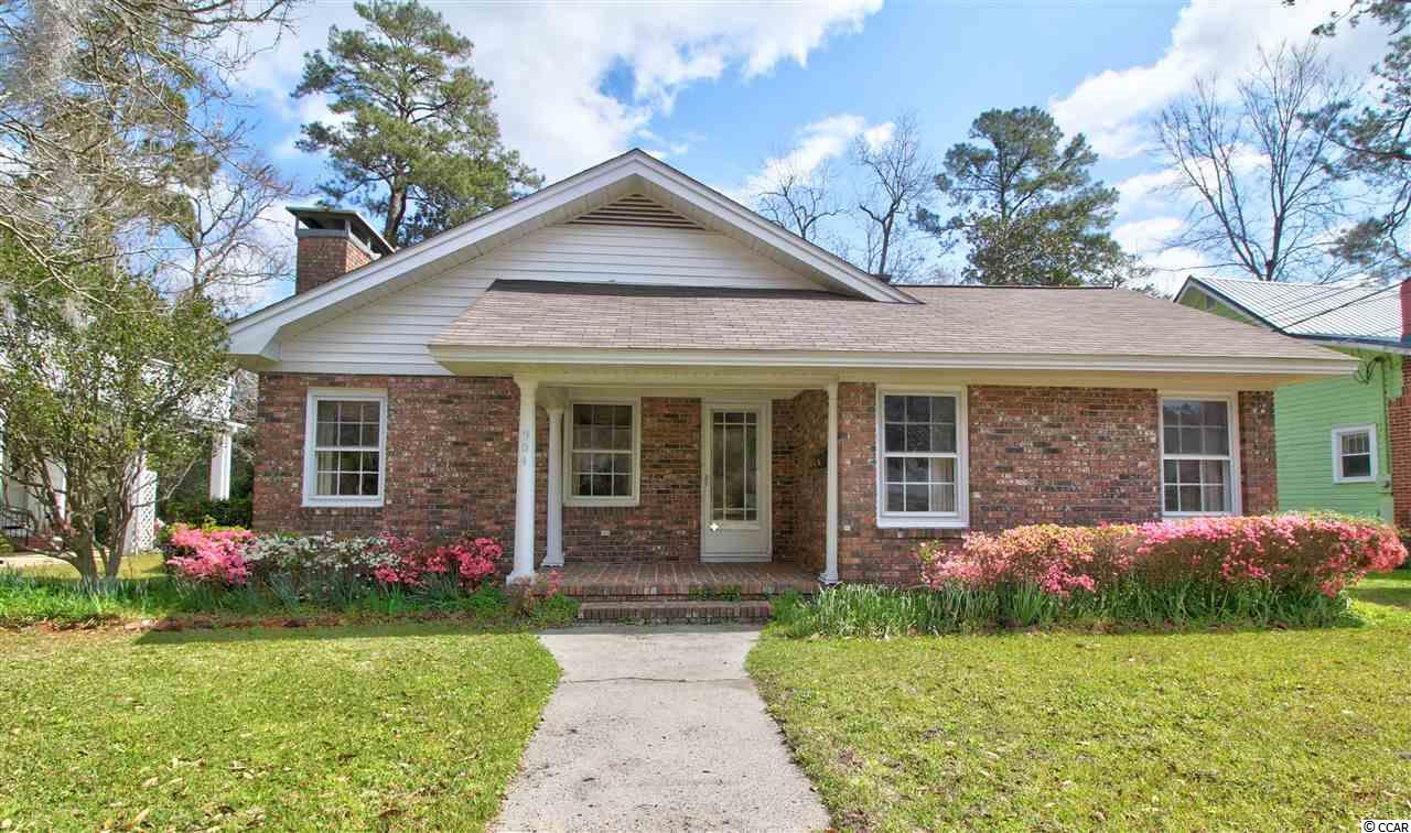 This 3 bed/2 bath home is located on one of Conway's much loved and desired streets with mature trees and azaleas. Don't let the front of the home fool you. It is a deep home with over 2600 heated square feet on the 0.21 acre lot with no HOA. The foyer welcomes you into the home where you immediately notice the beautiful hardwood floors. A formal dining room with chandelier, and a formal living room with a fireplace, give room for everyone. The large kitchen overlooks the family room that leads out to a Carolina room. The master bedroom has two closets, one being walk in. The master bath has a large garden tub, and a separate shower. Out back you'll find a huge detached building measuring 54' x 11' with 220 amp electrical in place. This would be a great artist's studio, man cave, workout room, or storage space. Live in the heart of downtown Conway and walk to the Riverwalk, the Theatre of Republic, restaurants or the library.