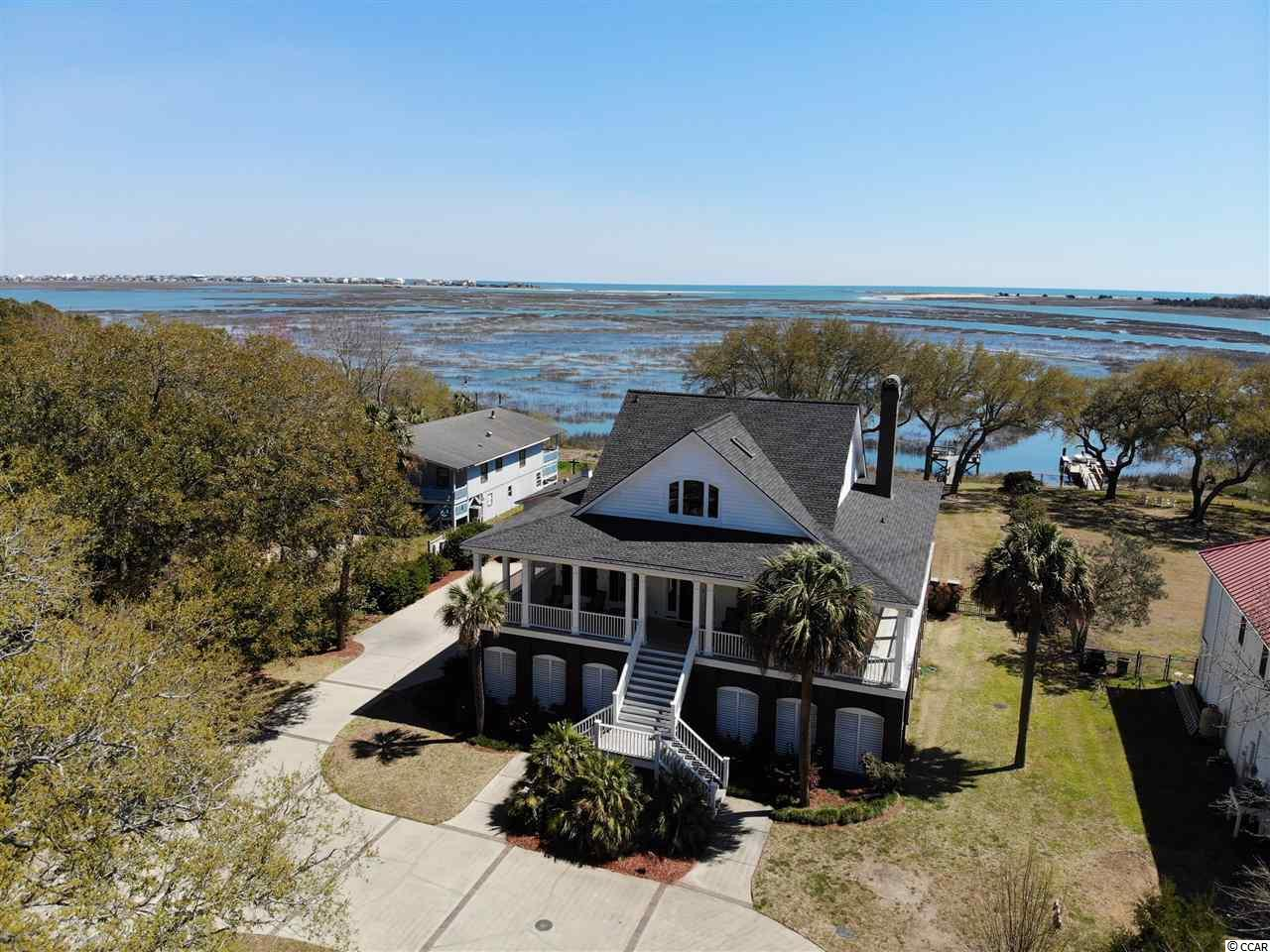 Wow what a rare opportunity to own approximately one acre of waterfront property in the heart of historic fishing village Murrells Inlet, SC! This extraordinary property has much to offer. Timeless appeal holds true in this plantation style home with guest house. Priceless live oaks invite you in to this fascinating property! A well thought out design offers wall to wall windows and doors that are surrounded by southern porches or decks! From the moment you enter your eyes are drawn to the unrivaled breathtaking views of the inlet, channel and ocean! Beautiful hardwood flooring leads the way to the light filled kitchen, dining, and living space. This open concept is perfect for entertaining! The kitchen offers white cabinets, granite counters, Sub-Zero refrigerator, double ovens, wine cooler, ice maker and cook top. The living area has an amazing brick fireplace made from the brick of the old home that was previously built on the property! The Carolina Room is spacious and flows seamlessly from the living area. Two guest bedrooms have hardwood floors, private baths and plantation shutters. Both have doorways leading to the wrap around porch! The private master retreat is a gracious size and offers a wet bar, wine cooler, walk-in closet, en suite bath and a private balcony with a captivating view! The master bath has double sinks, jetted tub and frameless glass shower! Just across the hall is an addition bonus space with two large closets. There are endless possible uses for this space, such as an office, workout room or TV room. It also could easily be made into an additional bedroom and bath! The elevator accesses all levels. Underneath this amazing home is parking, a heated and cooled enclosed work area, half bath, and tons of enclosed storage area. When you add the gorgeous pool, private dock and a guest house, you have your own piece of paradise! The spacious guest house offers a one bedroom, full bath, eat-in kitchen and a private deck overlooking the pool and inlet! What more could you ask for?