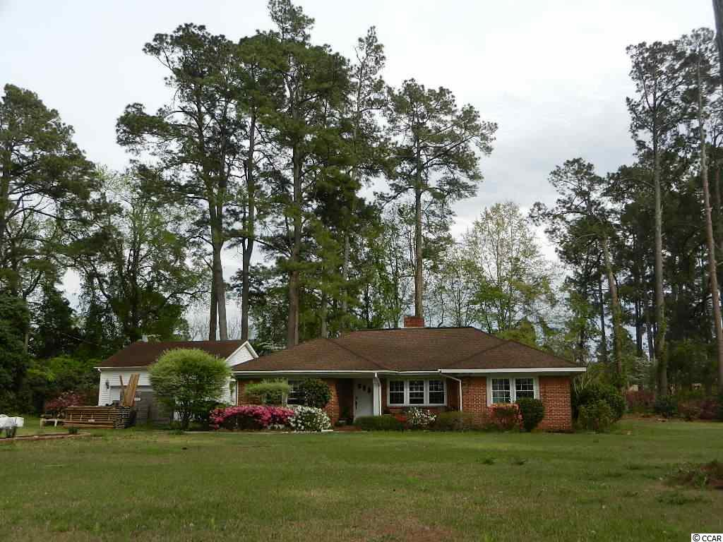 Great single level brick home with tons of character on a large corner lot.  This home features a large kitchen, formal dining room, wood burning fireplace in living room, library area, large master bedroom w/ garden tub and separate shower,  large rear screened porch, 2 car attached garage with plenty of storage, and ample parking room for boats, trailers, and all the toys that coastal SC living allows!  Located close to downtown Loris with easy access to coastal areas via Hwy 9 or 701.  Call today!