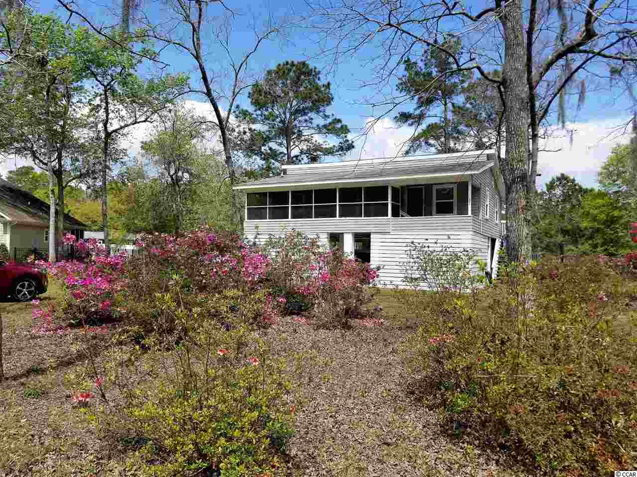 Want some peace and quiet close to the Murrells Inlet Marshwalk and ocean? Come see this almost 1/2 acre lot with beautiful old azaleas and moss draped trees abound. This cute two bedroom raised beach home has been remodeled and upgraded with brand new kitchen counters and stainless steel appliances, new light fixtures and fans, new bathroom vanity with new washer/dryer, new blinds, all new laminate and carpet flooring, newly painted - inside and out, and the garage area has been semi-enclosed. Disclaimer: All square footage is approximate and is not guaranteed. Buyer is responsible for verification.