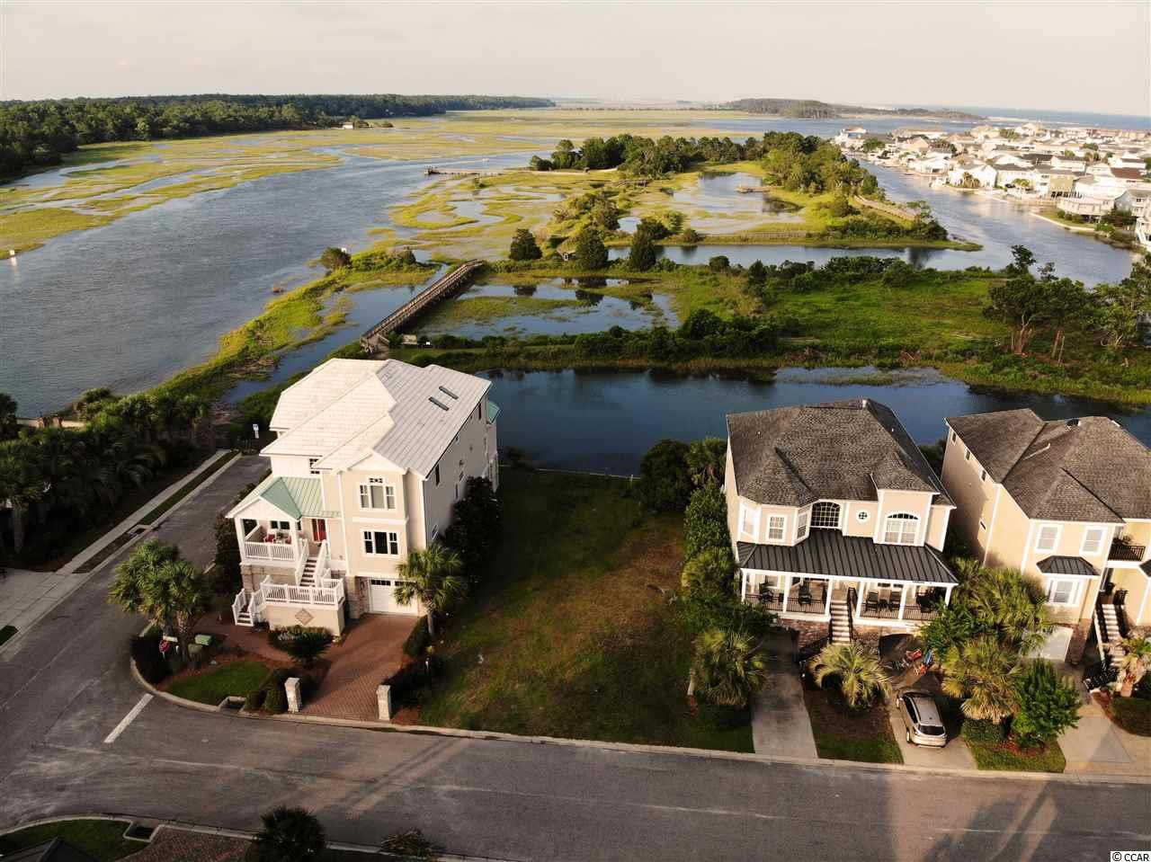 Waterfront Lot in the upscale island community of Heritage Shores in Cherry Grove.  Heritage Shores boasts beautiful, high end homes; underground utilities, public boat ramp and dock, nature trail for you to enjoy all the sights and scenes of salt water wildlife you  can ask for all only a few blocks to the beach.  Build your dream beach home in this exclusive water front community with amazing views!  This lot has a seawall and dock permit.