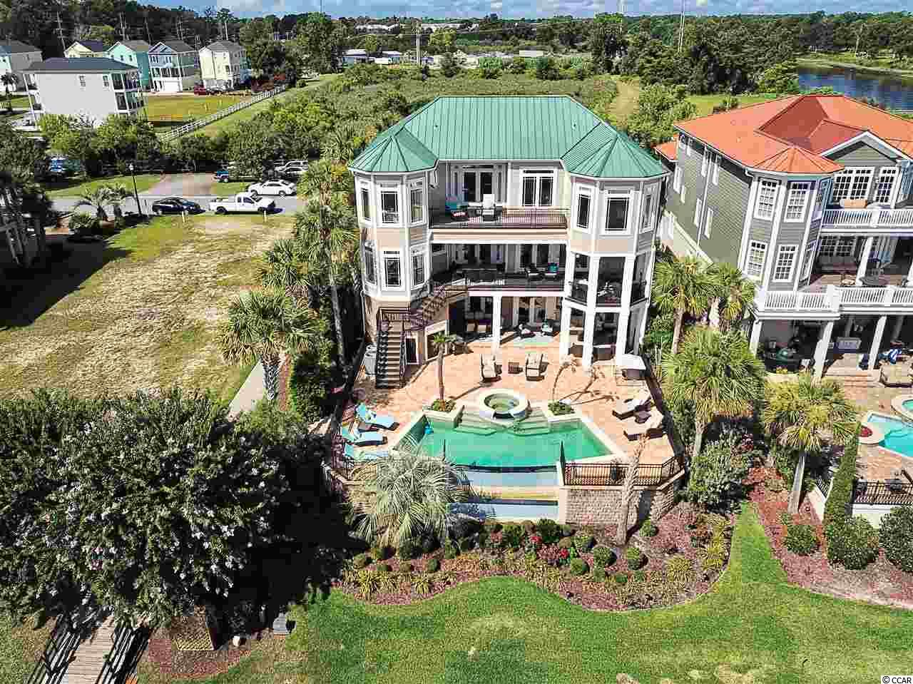 "Professionally decorated, fully furnished 4 BR/ 5 BA home with elevator, heated infinity pool and spa, overlooking the Intracoastal Waterway and Marina! Simply too many upgrades to list but includes, 24"" travertine tile flooring, custom carved cabinetry and paneled refrigerator, security system, custom-tiled glass seamless showers, upgraded lighting, Viking range, double ovens, double dishwashers, a 2nd kitchen on the ground floor with another dishwasher/wetbar/wine cooler, 2 Rinnai tankless water heaters, 500 gallon propane tank, 2 laundry rooms, central vacuum, dual rain showers in the master bath and a claw foot tub, loads of storage including a pool equipment room, and nook under the stairs currently used as a play space.  Freshly painted inside and out. Custom designed window treatments and bedding.  This home truly shows like a model and is move-in ready! Approximately 30 restaurants, a variety of grocery/drug stores, Walmart, and the beach are close by and can be accessed via golf cart!  Fabulous location and absolutely stunning home.  Do not miss this one."