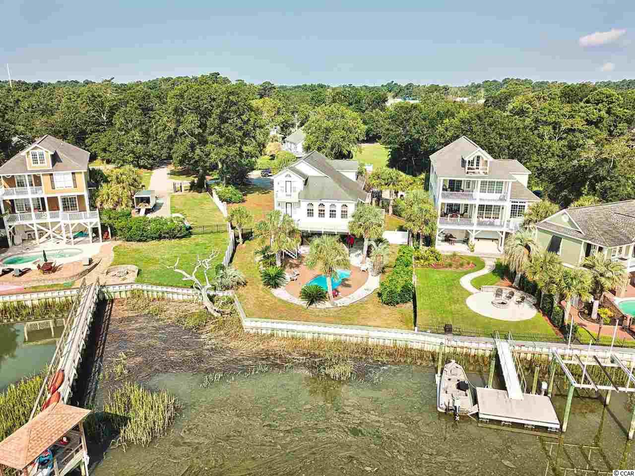 Fabulous views from the creek front home in the heart of Murrells Inlet! Live the Murrells Inlet lifestyle by walking to local restaurants like Beaver bar, Whiskey Fish, and many more. Seller has dock permit in hand and will be glad to build one for you, so you can take your boat to the marsh walk or out to the ocean! The home has 4 bedrooms and 2.5 baths, though one is being used an office right now. Stainless appliances, wood floors, huge great room, 1st floor master with large closet, and so much more. Plenty of parking underneath for all the toys and vehicles. Large back deck to enjoy the sunsets over the inlet.. Inground pool with huge decking as well.. This home is priced to sell and wont last! Set your appointment today!