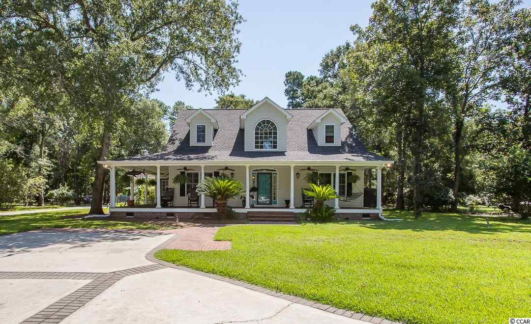THIS IS A RARE OPPORTUNITY TO OWN A CUSTOM HOME IN ONE OF MURRELLS INLET'S MOST SOUGHT AFTER NEIGHBORHOODS. Wilderness Plantation is a gated community, featuring large homesites, a private lake, and a community boat ramp with access to the Intracoastal Waterway. Southern Charm best describes low-country home, set in nature on a 0.73 acre homesite, among live oak trees, dripping with Spanish moss. Find your relaxation on your sprawling wrap-around porch, or screened back porch. Rocking chairs galore! This home has an extra large three-car garage (~1,100 SF), with a workshop and storage area for all those extras. This home is beautifully landscaped with a portion of the backyard fenced. The master suite is on the main floor, with an exquisite bath, measuring 27'x12', with heated floors, a large tub, fully tiled shower, double sinks, and separate vanity area, and let's not forget about the his and her closets. On the second floor of the main house, you will find a landing, perfect for reading, two bedrooms, a bathroom, and tons of attic storage. There is also an amazing bonus room, bedroom, and bathroom on the other side of the home. There are so many possibilities for this separate suite. Main living area is open and showcases a two-story foyer, dining room, kitchen open to the great room with bookshelves and a feature fireplace, and breakfast nook. And most impressive are the wood floors -- 19th Century Heart of Fir. Book your appointment to see this home today! You must see it to appreciate all its unique features. WELCOME HOME!