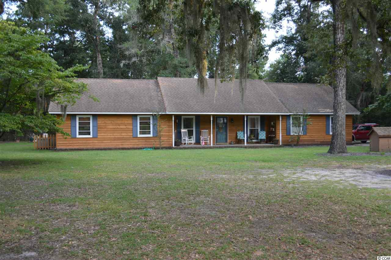 Here is your chance to live away from the crowd. You will have over an acre to yourself. It's just a few miles to the South Island Ferry or the Carroll Campbell Boat Landings. The current owner uses one of the 5 bedrooms as a weight room/office. For your outside enjoyment, there is a new back deck and an additional patio. There is a storage/workshop building in the backyard, with a chicken coop attached. The chickens WILL convey if the buyer wants them. There is also a fenced in area if you want to do some gardening. All stainless appliances in the kitchen. New paint and flooring in most areas. The wood burning stove in the den will keep you warm on a cold winter afternoon. If you own boats, trailers and RV's, there's plenty of room to park them all... and no HOA to deal with. A great location and a great home. Come see it as soon as possible.
