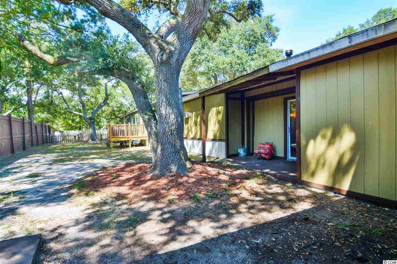Motivated Seller!  Bring all offers! Perfect multi-generational family home with 3 beds on the 1st floor, HUGE 1 acre lot, NO HOA and only 2 miles to the beach! This house is large enough to act as a home AND mother-in-law suite.  You can live on the single level side with 3 bedrooms/2baths including 2 antique wood burning stoves! Lovely, farm house style kitchen with barn door pantry, refurbished cabinetry, and countertops plus a skylight that brightens up the open area concept that includes dining-living room. Huge master bedroom with new floors, large walk-in closet and french doors leading to rec room. New roof,  new HVAC system in 2017 and 2 new side porches as well as being freshly painted.  Lovely, multilevel patio off the double door from dining area.  What a place to enjoy mornings under the large, live oak trees! As you leave the Master bedroom through double french doors, you are now entering newly constructed from studs inward, the recreation room with lovely mosaic granite floors, built in bar, pool table that conveys, and a sitting area with entrances from front of home and back patio.  Walking through wide open doorways from the rec room, you enter a serene sitting room with a wall flame insert.  Off the hallway on the left is the laundry with washer and dryer while on the right is a large, storage closet and an inside entrance to the separate rental home making maintenance easy without going outside!.  This original multi-story home is attached containing 4 bedrooms, bath, porch, cosy living area and kitchen (all furnished) with private entrance being used as spring/summer/fall rental   Separate outside entrance here too!  In addition there is a very large work shop behind the rec room.  This space could be easily converted into a 2 car garage. Located on over 1 acre of land this home is conveniently near everything Myrtle Beach and Murrells Inlet has to offer including: Murrells Inlet Marshwalk, Beaches, Ocean, Public Marinas, Public Landings, Publi