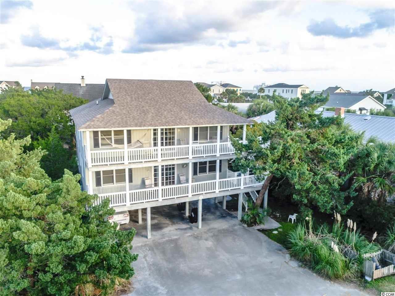 Amazing opportunity to own this Raised Beach Home on the island with views of Pawleys Creek ! The upstairs top level includes a full living area, kitchen, 2 bedrooms, and 1.5 baths. Middle level includes a full living area, kitchen, 3 bedrooms, and 2 full baths. The kitchens for each level are equipped with all appliances and have access to both back porch areas. Each floor level includes a large front porch and the rear porch. The bottom/ground floor level underneath features a studio apartment with a full bath. Located on the third row from the ocean, this property could be the perfect investment and rented in many different ways. Conveniently situated near all of the famous shopping, dining, and entertainment attractions the area has to offer, and only a few steps to the ocean. Plenty of parking and great porches! Short walk to the landing, which is only a few blocks north and you are just a quick walk away to the beach. Schedule your showing today !