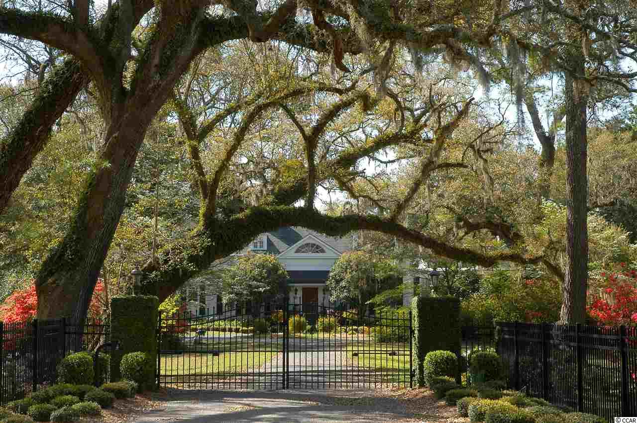 Picturesque Plantation home on 8+ park-like acres dotted with giant live oaks, old growth camellias, crepe myrtles, azaleas, tea olives and many specimen plants. The lawn slopes down to the Black River and faces south with long range views of three rivers and the old rice fields from ages past. The property was once part of a 3000 acre rice plantation. There are incredible views from most every window. Grand scale home offers very high ceilings throughout the first floor. The main three rooms are the banquet size dining room, formal living room, and large family room with Pecky cypress paneling. All main rooms on the first floor, including three bedrooms and kitchen, have beautiful wood burning fireplaces - a total of 7. The main rooms spill onto the huge veranda overlooking the property and take in the incredible views - from here you can see yachts on the Intracoastal Waterway. The master bedroom wing is a private retreat. Along with a sunny library and huge bedroom, there are multiple closets and two separate baths. Just off of the bedroom is an indoor pool with pecky cypress walls and ceiling. The pool has jets that allow you to swim against the current...great exercise without leaving your part of the home. The kitchen has beautiful granite counter tops and custom cabinetry, a large eat-in area with fireplace and servant stair to the second floor. Off of the kitchen you will find the pantry, laundry room, another bedroom and full bath, perfect for a live-in house keeper. The kitchen adjoins the huge sun-room. There are two more downstairs bedrooms with en-suite baths. Ascend the grand staircase and you will find four bedrooms and two full baths. There is also a very large media room / game room with multiple closets, this could be used as a 9th bedroom. In addition to the main house there is a lake with fountain, fish pond, caretaker's cottage, greenhouse, office/garage with full bath, garage parking for 4 cars and a two car carport. The garage spaces have room