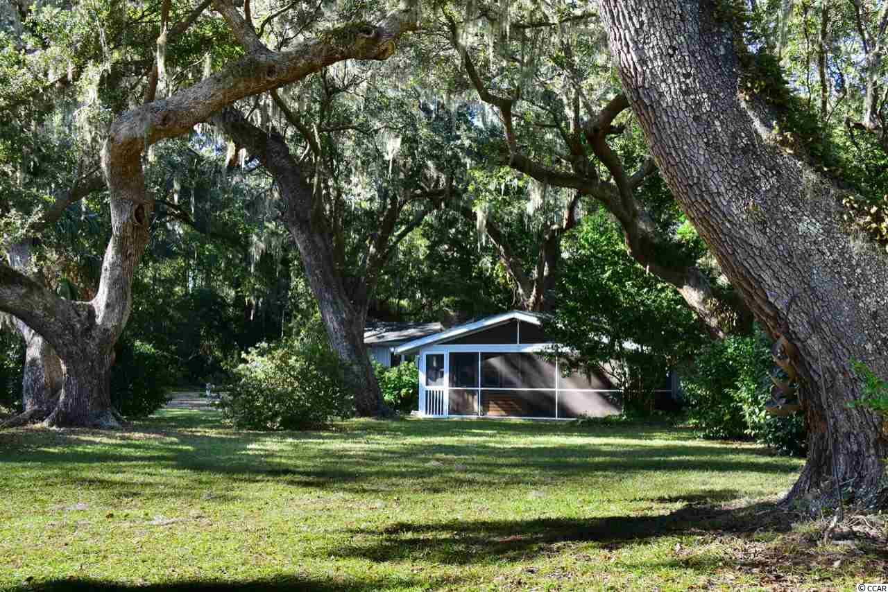 Been daydreaming much about strolling along the edge of the salt marsh, among your very own moss draped, 200 year old oaks? Dream no more, this Pawleys creekside cottage positioned upon a remarkable site laden with 18 impressive live oaks is just the dream come true! A quaint eclectic cottage takes full advantage of such views. Meander down to the creek and you'll find a brand new boardwalk and dock. Perfect for crabbing, fishing, paddle boarding, kayaking or boating and the chance to meet Hazel, a historic live oak tree. The main portion fo the cottage offers 2 bedrooms and 2 full baths and has been recently refurbished with up to date kitchen and baths yet a nod to the heritage of the home by preserving the wide plank wood floor and crafted brick fireplace. Large brick accent areas, 5 burner gas stove, stainless appliances, wine cooler, wood burning fireplace make this cottage more than comfortable. The expansive screened porch boasts brick floors and a prime vantage point with sweeping views through the moss to the creek. Woodwork and trim have been refreshed to give the spaces a craftsman finish. The separate 3rd bedroom/workshop with half bath is just steps through the breezeway! And to complete your place at the beach there's the perfect outdoor shower with a canopy of live oak arms above. There is ample room to expand the home, the lot is almost an acre! This location is irreplaceable and to say one of a kind is an understatement. The creekhouse with the Oak named Hazel is just the place to become a part of your family's legacy. Listing agent is related to the seller.