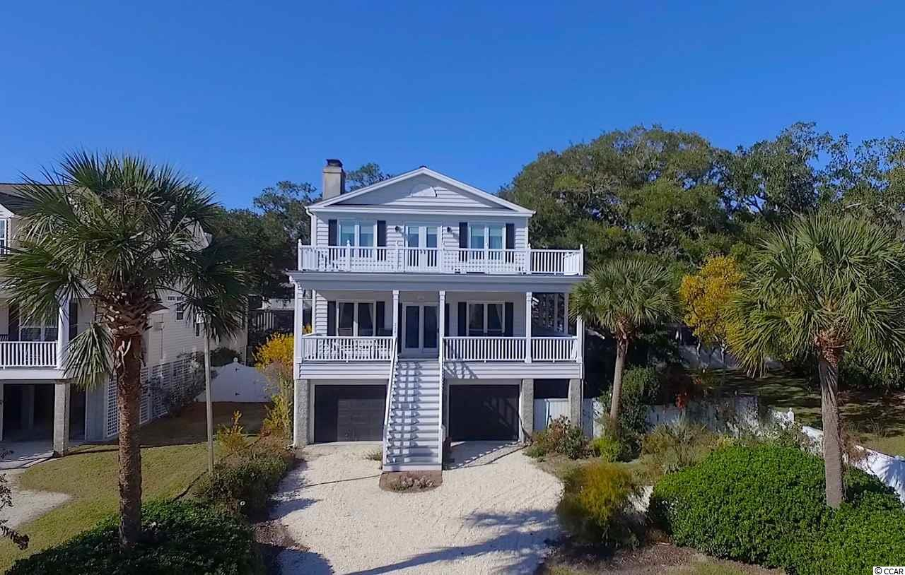 Oak Lea is a hidden gem. It is surrounded by beautiful mighty oaks, with Spanish moss delicately dripping from the branches. Located East of 17, you enjoy stunning inlet and ocean views along the boardwalk and dock. Inside 238 Berry Tree Drive, you are privy to quiet views of the inlet and oaks perfectly framed within the large windows. This home is a raised beach house, offering covered parking and storage. On the first living floor, there is a spacious family room complete with a large fireplace, a bright kitchen with a breakfast bar and eat in area which opens to a formal dining room that has a lovely view. A fourth bedroom and bath are also on the first floor. As you head upstairs, you may choose the stairs or elevator. Upstairs are three bedrooms and two bathrooms. The master bedroom is ample in size. It has a lovely sitting area by a fireplace, french doors that open to an upstairs deck facing the marsh, a bath and walk in closet. The laundry closet is conveniently located on the top floor close to the main bedrooms. This home offers opportunities to update it in your personal style and is priced as such. In addition to the amazing location and mighty oaks, Oak Lea also has a tennis court, an inlet side pool, a beautiful boardwalk and an amazing fixed and floating dock. It is the perfect location to launch your paddle board or kayak for a day's adventure. Be sure to check out the video tour of this property.
