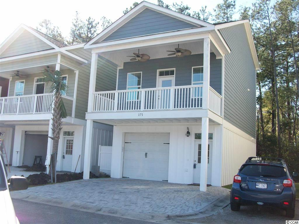 """**NEW PRICE** Inventory Liquidation Pricing! This RAISED BEACH HOME Is An Ideal Primary Home or Beach Getaway Located 1 Mile From The Beach! Enjoy Easy Living At Jamestowne Landing, Which Has An HOA That Manages The Homeowners Insurance, Exterior Maintenance, Trash Pickup, Cable TV, Lawncare/Landscaping, Pest Control & Community Pool That Is Only Steps Away. GOLF CART TO THE BEACH Straight Down Jamestown Rd/Atlantic Ave To Multiple Garden City Beach Access Points Where You Can Enjoy All The Restaurants, Garden City Pier, Arcade & Shops. Restaurants & Shops Are Within Walking Distance Of Community As Well. This UPGRADED """"SANDPIPER"""" Model Offers 3 Bedrooms, 3 Full Baths & Over 1800 Heated Sq. Feet. The Extended Bonus Room/4th Bed on Ground Level Would Make a Great """"Mother-In-Law Suite"""" W/ Full Bathroom & Leads To Private Stamped Concrete Patio. Master Suite is Located On Middle Level. The Top Level Has Two SPACIOUS Bedrooms W/ Jack-n-Jill Full Bathroom. As You Walk Through This Home You Will Feel The Beachy Vibe and Enjoy The Classy Touches Like Tile Master Shower W/ Glass Door, Enhanced Kitchen W/Extra Countertop & Cabinetry, Wine Fridge, Granite Tops, Soft-Close Drawers, Crown Molding. The Inviting Front Porch Has Overhang & Paddle Fans...All You Need Is Your Glass Of Iced Tea! This Home Has A DEEP One-Car Attached Garage & 2 Car Parking Pad... PLUS...Shared Parking Throughout The Community. Exterior Is Sturdy, Low-Maintenance Concrete Fiber Siding. Lot 501 Backs Up To Wooded Area. Pictures Are Of The Actual Home. This Home Is Bargain Priced At 2015 Building Prices and Builder Has Drastically Cut The Upgrades Cost (Ask Agent For Upgrades List) Which is SUBSTANTIAL SAVINGS To The Buyer. Several Other Floor Plans & Lots Available. Upgrades Available For Your Customization. """"4th Bedroom"""" is Bonus Room on Ground Level. Sq. Ft. Is Approximate & Not Guaranteed, Buyer To Verify."""