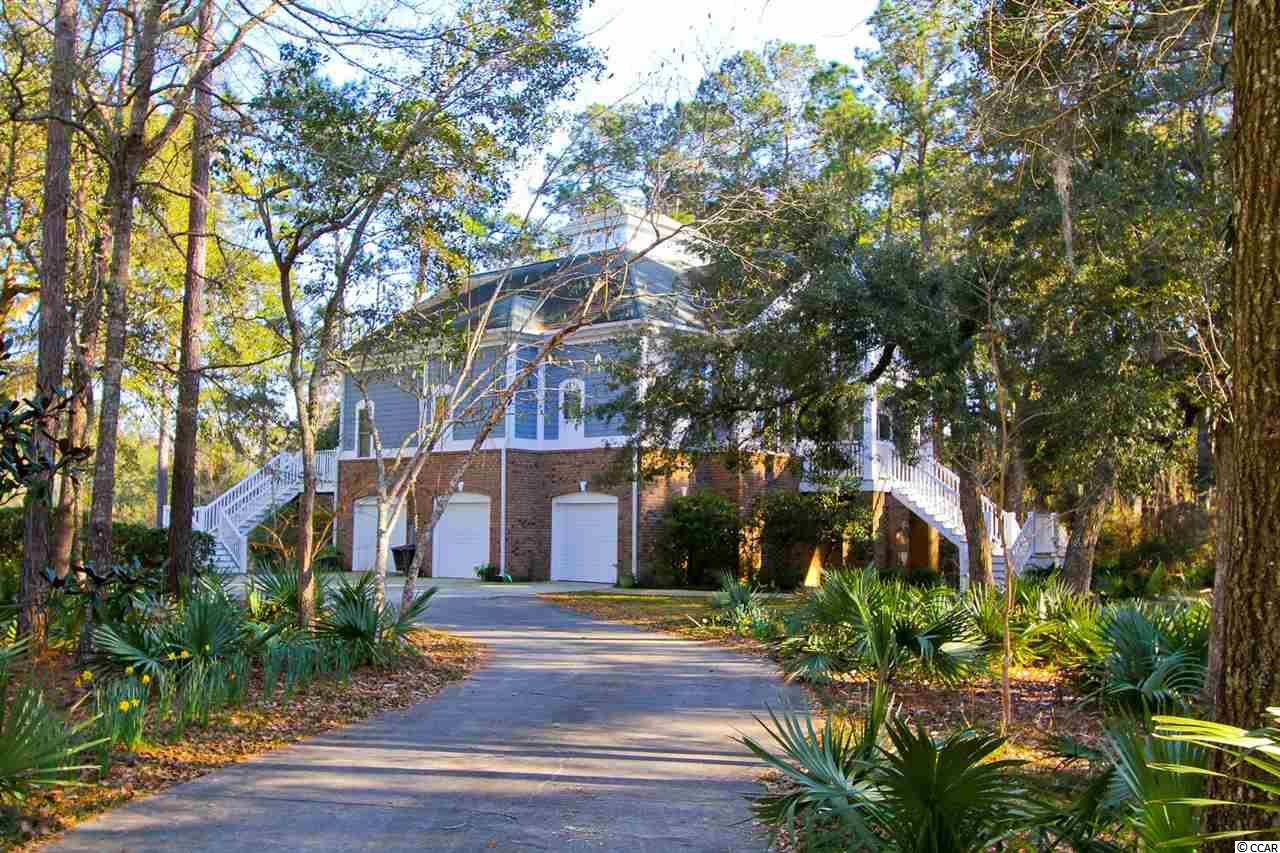 DeBordieu Colony – A beautiful lake front home with an open floor plan and separate, ground floor apartment, 204 Lantana is a perfect primary residence or vacation spot. The one-acre, secluded lot offers plenty of privacy and room to add a pool. Perfect for entertaining, the kitchen opens to the living room, dining room, sun room and den, complete with a separate bar. Also on the main living level is the spacious master suite, office, laundry room and powder room. Upstairs are two bedrooms, each with their own baths. From the sitting area, you'll have access to the deck, hot tub, and powder room. On the very top floor is the perfect place for a studio or sitting area, with access to the open deck with spectacular view. In addition to the spacious 3-car garage, the ground level features an apartment with a full kitchen and private entrance. Every bedroom has a private bath. Every living area has a powder room. The Kitchen features granite countertops, custom cabinets, Thermador oven, Subzero refrigerator, pantry, and microwave. The wine refrigerator and icemaker are located in the bar, in the den, just off the kitchen. The master bath features a long, 2 sink vanity, and a huge tile shower. Other features of this spectacular property include: Gorgeous Sepela Mahogany floors, Tile in bar and baths, carpet in bedrooms and office, New Anderson doors, built in cabinetry in living room, dining room and office. There is a gas fireplace in the living room, and a wood burning fireplace in the den/bar. The house is wired for sound system, and prewired for a generator. DeBordieu Colony is an oceanfront community located out an hour north of Charleston, South Carolina, just south of Pawleys Island, featuring access to over 6 miles of secluded beach, private Pete Dye Golf, a Tennis & Fitness Center, an Ocean Front Beach Club with casual and fine dining, saltwater creek access to North Inlet and the Atlantic ocean, a 24/7 manned security gate, and luxury homes and villas surrounde