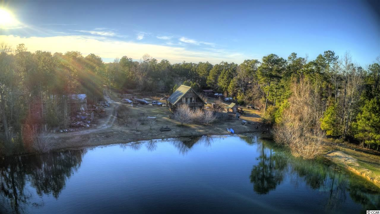 """If you're looking for land to develop or your own private oasis close to the beach, this is it! This 3 bedroom/2 bathroom home is perfect for any farmer, equestrian, hunter or fisherman! It sits on more than 43 acres of land and is just a 15 minute drive to the beach, 1.5 miles from the Waccamaw River Landing at Reaves Ferry, and a 10 minute drive to downtown Conway. Built in 2009, this steep A-frame home is solid as a rock with 11'6"""" studs and is well insulated with 6"""" walls and a brand new HVAC (July 2019). The interior is all oak, pine, and poplar wood, including the interior walls (no sheet rock here!), ceilings, kitchen cabinetry and kitchen countertops. Downstairs, you find both tile and laminate flooring. It's also where you'll find the laundry room, a bedroom, the living room (with a wood heater that works and conveys!) and kitchen. The bathrooms were completed with red oak. The master bathroom has a large tiled shower/soaking tub combination. Both of the bedrooms upstairs have large walk-in closets. There's also a 650 sq ft attic floored for storage off the master bedroom. Both the master bedroom and living room face to the east and have large porches off of them that you can sit on, relax and take in gorgeous sunrises as well as views of the five acre, spring fed pond behind the home. In the middle of the pond is an island that's 50ft in diameter. The pond is stocked with bass and brim, so if you're into fishing, you're all set! You've got complete privacy with the property being located at the end of a long, private, gated driveway (with an electric gate); opening up to the home that's surrounded by apple trees (Dorsets, Red & Yellow Delicious, Granny Smith, and Crabapple), peach trees, plum trees, Crepe Myrtles, holly, and wild muscadine grapes. The timber on the property is oak, pine, poplar, and some cedar, which the owner used to make the majority of the furniture in the home. Beyond the pond is the majority of the land, which is currently used for hu"""