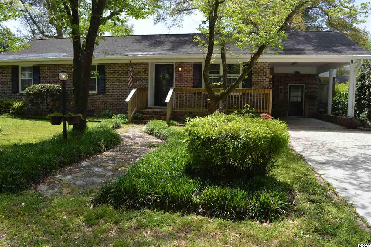 """This adorable all brick cozy and older home has so much charm and character! It sits on a very large and private lot east of 17 business in the Garden City/Murrells Inlet area. There is no HOA so that gives you the freedom to park your boat, trailer or camper! There is a chained link fence that surrounds the entire back yard with a gate so you may park either on the side of the house or in the back yard. If you are looking for an additional garage/workshop this home has that also! A new 20' x 25' sturdy metal building with a garage door sits on a concrete pad in the back yard. The possibilities are endless ,as it could be used for a work shop or storage, the choice is yours. There is a conduit elbow in place in the concrete pad for future electrical service to this garage. Talk about location, location! Public boat ramp is just up the street and it is only a short golf cart drive to the blue Atlantic- now that is sweet! This beauty has been updated and is in wonderful move-in condition! Home is all brick and has vinyl soffits which makes this house so easy to maintain. As you enter, you are greeted by a very open and inviting floor plan which you will appreciate. The living room flows into the kitchen area and is so nice for every day living. The original kitchen was removed and now there is a new kitchen with 42"""" white cabinets, new counter tops, new stainless steel sink and faucet. All newer stainless steel appliances , bead board back splash and new light fixtures. A large movable work island has been added and features a butcher block counter top. This not only gives you extra work and storage space but also is where you can sit and enjoy your meals. Attractive wood-look Pergo laminate flooring in living, kitchen, hallway and one bedroom. Crown molding in all rooms except bedrooms. All freshly painted walls through out. Master bedroom has double closets. Original master bathroom has been updated and enlarged and has a very pretty double sink area, new commode an"""