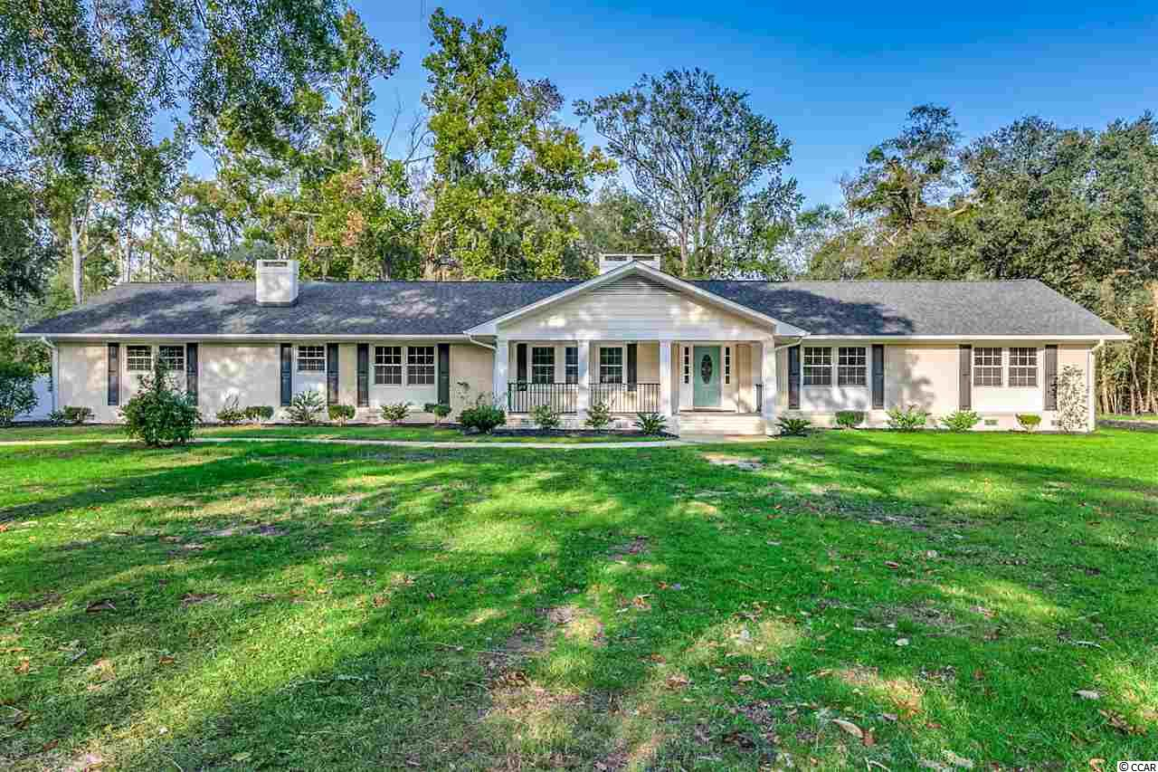 Absolutely gorgeous! This huge 4 bedroom, 3.5 bath solid brick ranch has been renovated to the studs and updated throughout! Fantastic central Conway location, two acres, with Kingston Lake in your backyard!!! From the formal entry hall, accented with an octagonal tray with crown molding and a chandelier, to the rear porch with vaulted pine ceilings, the utmost care and craftsmanship has been poured into this lovingly restored home. The formal living room is defined by its coffered tray ceiling and stunning fireplace, which flaunts a marble tile surround.  The kitchen has been completely redesigned, with beautiful solid wood raised panel cabinetry with soft-close drawers and extraordinary marble counters, plus Jenn-Air stainless appliances, including a down-draft gas range and built-in microwave drawer. There's also a butler's pantry, easily accessible from both the kitchen and the dining room, with a beverage refrigerator.  The walk-in pantry is to die for, with more than ample storage, and the huge laundry room, just across the hall, is lined with cabinetry for even more storage. Adjacent to the kitchen is the casual family room, with another impressive fireplace that has the perfect mantel for displaying your seasonal decorations and family photos, and a tray ceiling with more crown molding, recessed lighting and a silk drum chandelier. The bedrooms are off on their own private hall, and are all spacious and charming. The master suite, under a tray ceiling with crown moulding and an elegant chandelier, is at the back of the home and boasts a wall of closets plus a walk-in, outfitted with built-ins. Two huge windows frame the amazing view of the river beyond. The master bath has a glass-enclosed tile shower and two separate vanities that have the same cabinetry and incredible marble countertops as the kitchen. One guest bedroom is a suite, with its own bath, and two others share a Jack-and-Jill bath between them, and both baths are outfitted with the same graceful details as the master bath. A large screened porch is located off the family room, the perfect place to enjoy your coffee or cocktails and enjoy the view of the huge backyard and Kingston Lake. Set back from the road, the generous front yard accents the grandeur of this beautiful home. Minutes from downtown Conway's charming restaurants, boutiques, RiverWalk and theater, and about a half-hour to the attractions of Myrtle Beach.