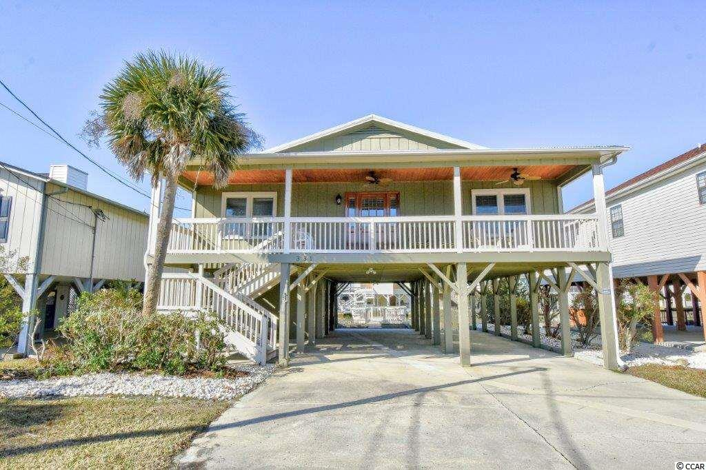 Welcome to The Wavecrest! Located on one of the widest channels in Cherry Grove, this classic raised beach home has been beautifully maintained and recently updated with a new hot water heater, new HVAC in 2017, a reinforced boat ramp and bulkhead, new gutters and new plumbing was just installed from the street into the house. Completely furnished with delightful beach accents throughout, this 4 bedroom 2 bath home features laminate flooring in the spacious living room which is adjacent to the large fully equipped eat in kitchen with abundant cabinet and counter space plus a breakfast bar. In addition, both baths have vanities, there is a separate laundry room with washer and dryer and there is plenty of closet space plus a ground floor storage space perfect for all of your beach toys and golf equipment . Outside, you and your guests have the option of relaxing on either the expansive front porch or rear screened porch which overlooks the channel. Both porches have dual ceiling fans and are accented with stained tongue and groove ceilings for a true coastal feel.  A private walkway leads to the fixed deck extending over the water for incredible views of the channel and the home also has its own boat ramp! Great location-just minutes from shopping, dining, entertainment and the beach.  Whether you are searching for a primary residence or the perfect beach retreat, this is a wonderful opportunity to finally have your dream home on the water! Don't miss it!