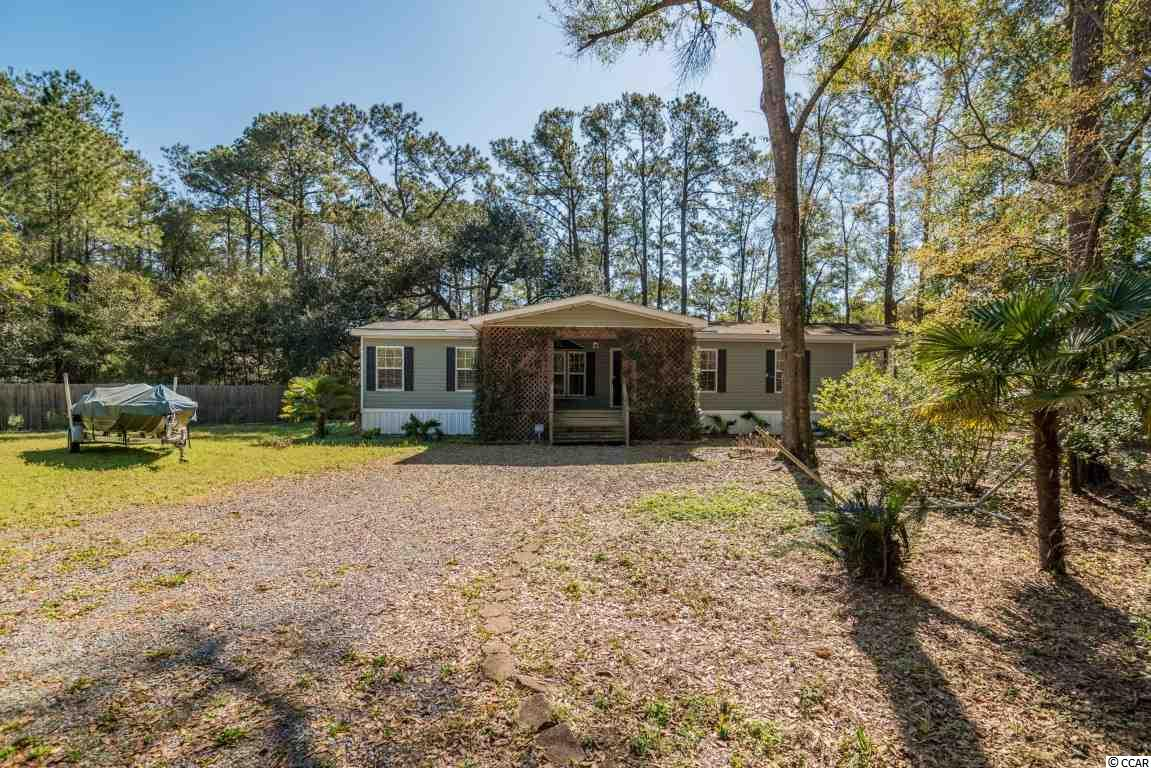 This home is centrally located in Pawleys Island on a large nearly one acre secluded lot. Three bedroom two bath plan with formal living, master suite, two porches and a deck. Gently used as a second home and in great shape this home enjoys a huge fenced yard with no restrictions. Close to public boat landing on waterway and short drive to beach.
