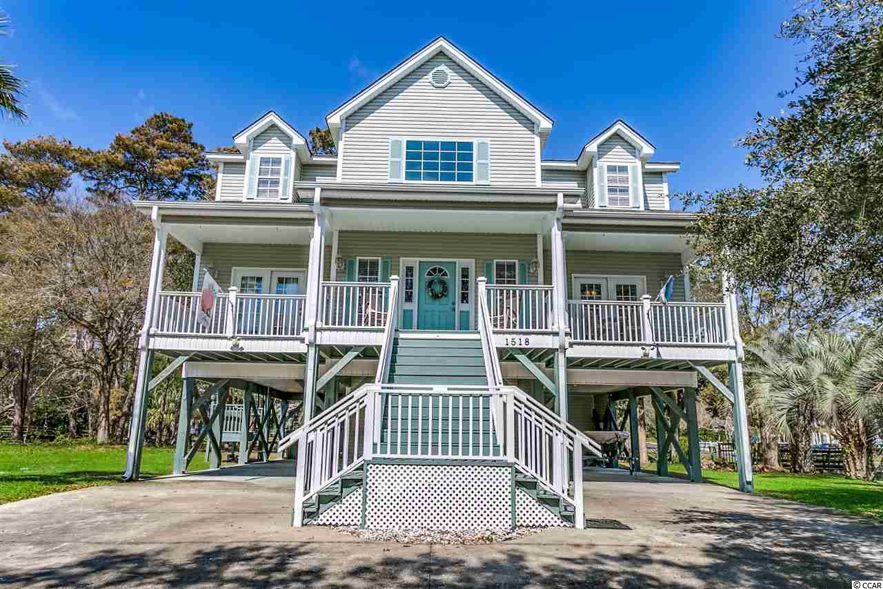 Closing scheduled for 8/29/19. 1518 North Palmetto Drive is a custom built five bedroom, 4.5-bathroom, 3074 heated square foot, single family raised beach house, 800 feet to the beach in the Town of Surfside Beach. Situated on Magnolia Lake this two-story home has a welcoming, full width covered front porch, multiple ground level storage rooms with room for a golf cart, parking for at least ten cars, and low maintenance landscaping with an irrigation system. The corner lot borders a serene lake with beautiful hardwood trees and enough space to add a pool. The home, constructed in 2005, has the finishes and attributes you're looking for in a primary residence just two short blocks to the beach. The generous two-story living room is the hub of the home that leads into a large eat-in kitchen, laundry room and pantry, formal dining room with wet bar, Carolina room and first-floor master suite. The main level features crown molding throughout and oversized tile floors in all living and dining areas. The home's kitchen has custom glazed cabinetry, breakfast bar and sells with all appliances including separate freezer and washer/dryer. The Carolina room is all windows and provides tranquil views of the lake. The master suite encompasses the entire side of the home, has access to the front porch, a bathroom with two sinks and large vanity, separate shower and garden tub, linen and toilet closets and a large walk-in closet. Upstairs there are four bedrooms and three ensuite bathrooms. Access to the fifth bedroom is through a bedroom. Under the home, there is versatile space for the parking of cars and boats as well as outdoor living space with a sink and counters along with a refrigerator. Both outside storage rooms are large enough for golf carts or motorcycles and could be suitable for a workshop. The home has been well cared for and is turn key ready for you.