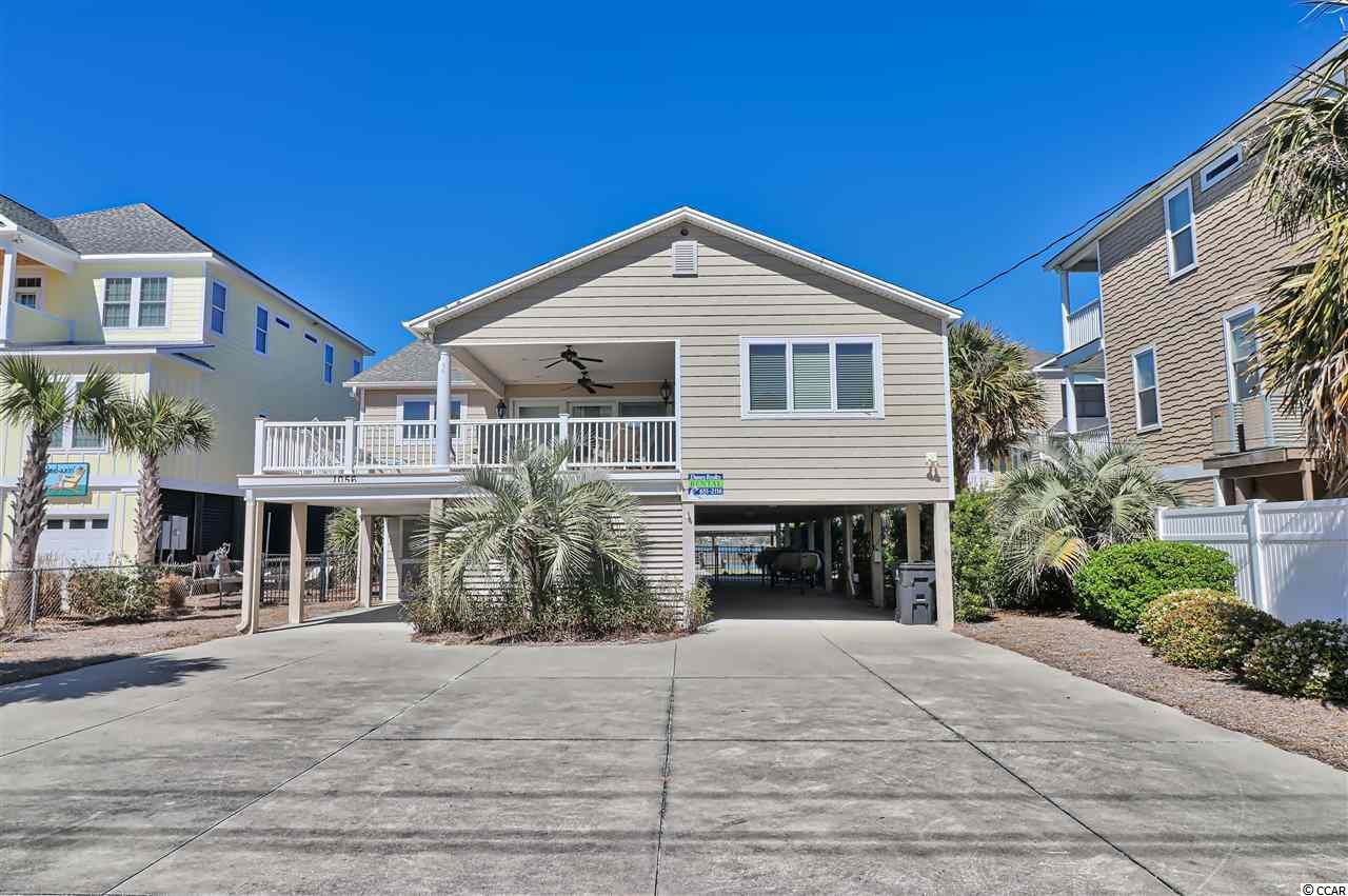 On the creek and across the street from the beach makes this 4 bedroom and 3 bath home the perfect spot for a beach vacation!  Large deck and porch on the front is ideal for enjoying ocean breezes!  The back porch and deck is the best place to enjoy amazing sunsets over the creek.  The open floor plan has high ceilings, fireplace and large kitchen for entertaining friends and family.  The master suite has been enlarged and there is an oversized guest room on the first floor with a sitting area opening up to marsh views.  The dock has a covered area and boat lift!  This is a fisherman's dream with deep water even at low tide!  The double lot has plenty of room for a pool!  Walk across the street to enjoy the rarely crowded Garden City Beaches.  Jump on your boat and enjoy a day of fishing or cruise over to the Murrells Inlet Marshwalk for dinner!  You can have it all!