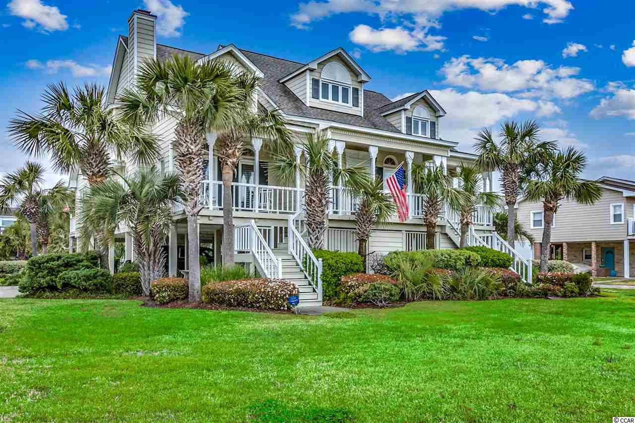 This 3br/3.5 bath raised beach home located in the absolute heart of the prestigious Ocean Drive & Tilghman Estates area section of North Myrtle Beach is in excellent condition and ready for it's new owner.    When you sit down to relax on your front porch, you will be taking in some of N. Myrtle Beach's best ocean views.    This custom built home has only had one owner and has been extremely well cared for.   From the moment you pull up to this great home, you are greeted with a spacious  corner lot with room to spread out and professional landscaping.   When you walk through the front door, you are greeted with gorgeous heart pine wood floors running throughout the entire home(except carpet in the bedrooms).   Cathedral ceilings, lots of windows with plantation shutters allowing in tons of natural light, wet bar, and a gas fireplace offer you a beautiful living/family room for your entire family to spread out.   As you walk into your spacious kitchen you are greeted with tons of cabinet and counter space, lots of windows for tons of natural light coming into the house, and a breakfast nook right off of the kitchen.    If you are someone who likes to entertain, make sure to use the formal dining room for all occasions.    The master bedroom is located on the first floor of this home offering large his and her walk-in closets.   As you enter the master bath, the skylight allows so much natural light in.  It also boasts dual sinks, vanity, walk-in shower, and a whirlpool tub.  Your family or guests will enjoy their own bedrooms and private baths upstairs.   If you are someone who likes to work from home, make sure you set your office up in the loft upstairs in front of the window that gives you endless ocean views.     You have to see it to understand!     Some of the other great features of this home are:   New Roof 2018, HVAC approximate 3 years old, extra large storage under this home, great use of all space for storage throughout this home, tons of room for additional parking, powder room for your guests, reverse osmosis water filtration system in kitchen, solid surface counters, security system, front and rear porches, many areas under the home for the family to relax and enjoy, and most importantly.....directly across the street from the beach.    When you walk out of your front door, within seconds you will be walking along the edge of the gorgeous beaches that await you in North Myrtle Beach's famous Ocean Drive section.   You are short golf cart ride from all of the fun that happens on NMB's Main Street as well.    If you have been waiting for the perfect opportunity to live in one of the Grand Strand's most desired spots....your wait is over.   This is it!