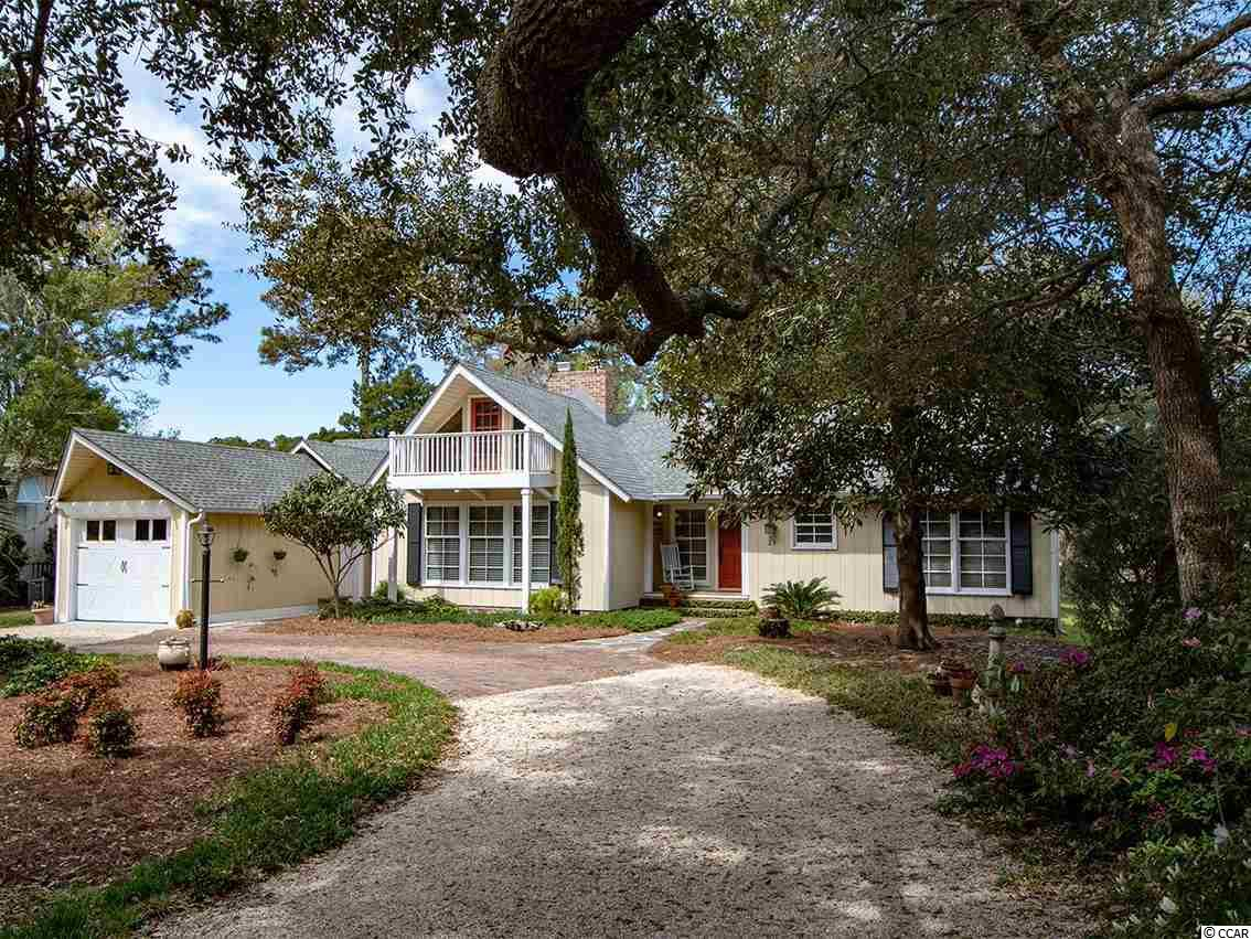 29 Lakeshore Drive is located in North Litchfield, a well-established Beach Side community on the South Carolina coast known for its stable beach and easy access.   This old-style craftsman-like One-level 3 bedroom, 3 bath beach cottage is located on a serene lake and only 3 blocks to the wide sandy beach.  The home has been well maintained and updated thru the years, including new roof (2016) and HVAC (2019)  Vaulted wood & beam ceilings in most every room, gas fireplace, formal and casual dining areas, wide-open Great Room with towering cathedral ceilings, split bedroom plan, home audio system, hardwood floors and lots of character.  An upstairs loft offers a cozy office or extra sleeping area. Spend hours relaxing and enjoying nature from the screened porch or patio that overlooks the water and undisturbed natural area.  There is and a big yard from which you can launch a canoe for a quick cruise across the lake.  Enjoy the convenience and privacy of a large Sun Deck on the rear of the house to work on your tan.   Full-time residents and 2nd home owners seamlessly co-exist is this relaxed neighborhood.  Short term vacation rentals are allowed but this house has been a full-time residence for many years.  No HOA fees unless you want to be part of the voluntary association.  The North Litchfield community is bordered on the north by Huntington Beach State Park giving you miles of beach to stroll along.  Close-by outside activities include award winning golf, kayaking, fishing,  boating, walking and bicycling.  Quaint local shops, sumptuous restaurants, grocery stores and medical services are nearby as well.  Historic Georgetown is just a 15 minute car ride away.  Conveniently located just 30 minutes south of the Myrtle Beach International airport and all the tourist attractions in the area, or enjoy a day trip to Charleston.  Go ahead and give yourself permission to totally immerse yourself into the South Carolina Lowcountry lifestyle and call today for a tour of t