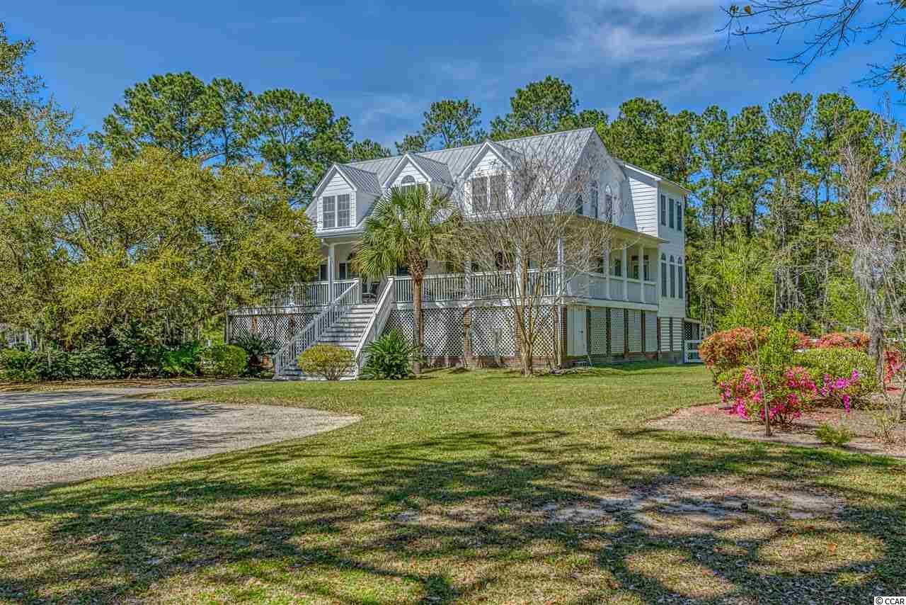 Captivating lowcountry style in Waverly Plantation.  Situated on over an acre with 285 feet of waterfront on Waverly Creek with a 20 X 8 floating dock. Just a short boat ride to the Intracoastal Waterway and only minutes from the beach.  This alluring property is surrounded by mature live oaks and beautiful azaleas. Upon arrival you are welcomed by a gracious front porch.  Once inside you will notice the open floor plan with flexible options for style, design and livability.  As you enter, the Australian cypress floors and fireplace extend the southern charm. With windows abound, the natural light pours in bringing inside all of the natural beauty of the outside. The master suite offers dual sinks, whirlpool tub, separate shower and large walk in closet. Upstairs you will find two bedrooms, a large family room and Carolina Room that could be a 5th bedroom. The main level offers an abundance of space for additional living area, office or guest suite with private bathroom. The myriad of outdoor space includes a large screened porch, covered cabana, additional covered area for grilling or seating around the kidney shaped pool.  Additional features include a split rail fence around entire yard, irrigation system with well, concrete fiber siding, metal roof and bulk headed seawall. The private dock, pool, outdoor living space and water views offer a unique opportunity in Pawleys Island for a wondrous and relaxed coastal lifestyle.  Just minutes to the beach, fine dining, remarkable golf courses and shopping.  Historic Charleston is just an hour drive and Myrtle Beach Airport and attractions are only 30 minutes away. Gracious, lowcountry living in the heart of Pawleys Island.