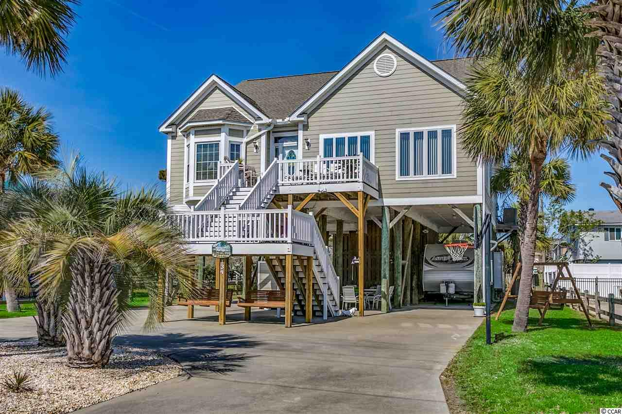 For the discerning buyer looking for location, condition, and amenities, this property checks all the boxes. 134 Cypress Avenue is not only a beach house, it's a home, and you'll notice the difference. Located 400 feet from one of the most beautiful stretches of beach along the Grand Strand in Garden City Beach, this four-bedroom, 3.5-bathroom, custom constructed home with 3406 heated square feet is not a rental property, and it shows in its condition. The main level of the house includes a flowing floor plan with the living room, dining room, family/game room, kitchen, laundry, half bathroom, and master suite.  All the living areas have five-inch-wide and ¾ inch thick hickory wood floors. The kitchen, bathrooms, and laundry room have tile floors, and the bedrooms have carpet. The updated kitchen has solid maple cabinets, granite countertops, and stainless-steel appliances. The master suite has an ensuite bathroom featuring twin walk-in closets, two vanities/sinks, whirlpool tub, and separate shower. The game room features a wet bar and eight-foot one-piece slate pool table. Upstairs there are three more bedrooms all with ensuite bathrooms, a bonus room off a bedroom and attic storage galore. The property is situated on a large lot with room for a pool, includes two outdoor showers and a toilet, two storage rooms and a large workshop, 17-foot ceilings with adequate space to store all your toys and has a 30-amp dedicated motorhome power supply. There is a large sundeck off the kitchen with views of the marsh and leads to the private backyard and hot tub. The front porch has two levels with limited views of the ocean. The landscaping is generous but low maintenance. The construction of the home is superior to any local codes. It was built to last and shows owner pride inside and out. Whether you're looking for a primary residence, second home or vacation rental, make sure you check out this excellent example of craftsmanship. Garden City Beach is a small traditional b