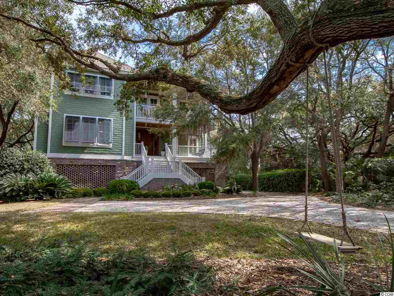 """Created to complement your coastal lifestyle, this three-story wonder in Debordieu Colony beckons. From the upper level providing a serene space for reading, exercising, crafts and/or birdwatching as well as access to an observation deck with an extraordinary ocean view to the first floor with an awesome bunk room for the kids...this home exudes spaciousness and invites you to enjoy all that makes Debordieu so special. SECOND FLOOR/MAIN: A vaulted and beamed ceiling with a Key West style fan anchor the Great Room which opens to the Dining Room and Kitchen where family and friends can reconnect each day.  A double-sided GE Monogram refrigerator/freezer, 2 Bosch dishwashers, Thermador gas range,  oven, microwave and warming drawer provide for entertaining """"at it's best.""""  The large Master Suite provides an ideal retreat with walk-in closet, separate vanities, a garden tub flanked by built-in cabinetry as well as tiled shower and water closet.  FIRST FLOOR:  A large den anchors this floor which has four ensuite bedrooms, to include a bunk room. A laundry room with an additional dryer is just one of the many """"extras.""""   GARAGE LEVEL: A separate exercise room as well as enclosed storage completes this space which allows not only for parking but also for golf carts, boats, and sundry items for outdoor and beach activities. The elevator provides access to the first and second floors. Grand vistas of the live oaks and private lagoon are afforded from every level.  Bahama Shutters provide privacy as you enjoy your """"outside"""" world on the many porches which are complete with a mosquito misting system are also features of this spectacular home. Debordieu Colony - a private 2700 acre community offering miles of beach, championship golf, professional tennis and fitness center, two swimming pools with gazebo bar, onsite nature preserve, bike paths and walking trails as well as fine or casual dining at the Club House and/or Beach Club. A community boat landing provides access to No"""