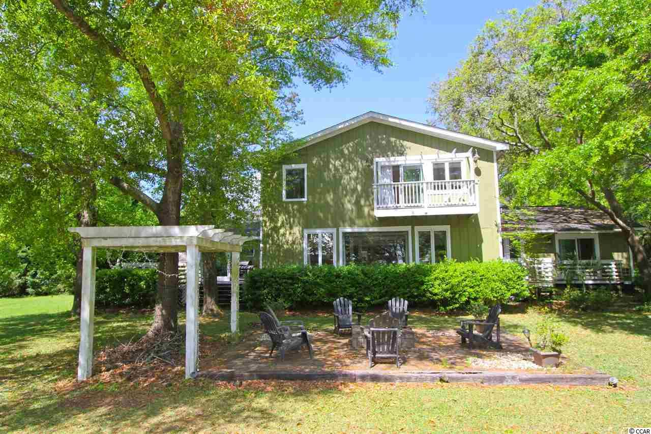 Marsh View with attached, private, ground floor apartment located right in the middle of Pawleys Island and Murrells Inlet where you will enjoy the best of both worlds! Huntington Marsh is a great neighborhood, hidden away just north of Brookgreen Gardens and the beaches of Huntington State Park! Close to everything Murrells Inlet has to offer, 5464 Huntington Marsh is right off the Bike the Neck Trail, close to boat access at Oyster Shell Landing, and convenient to the fabulous dining at the Marsh Walk of Murrells Inlet. The totally open living space coupled with the decks and firepit makes it perfect for entertaining a large crowd both inside and out! As you enter the foyer, you're immediately drawn into the welcoming Living Room with vaulted ceiling, the spacious Dining Area, and the Den, with wet bar, wine refrigerator, study area, and fabulous marsh view. That view is also spectacular from the breakfast nook, right off the incredible kitchen offering double ovens, 2 cook tops, one gas and the other propane, GE Profile and Jenn-air appliances, and a ton seating space at two counter bars. In fact, if you're in to exhibition cooking, this is the perfect spot! Right off the kitchen is the mud room leading to the garage, laundry, huge pantry, and powder room. Also on the main level are two guest suites, each with their own private bathrooms.  Upstairs is the Master Suite, and a large, loft, office space that could be made into a 5th bedroom with access to an existing full bath. The Master Suite features a beautiful balcony view, walk-in closet, a double sink vanity, big garden tub and separate shower.  5464 Huntington Marsh also offers a ground floor, separate but attached apartment with private entrance that boasts that same great water/marsh view, private entrance, a kitchenette, full bathroom and separate bed and seating areas!  Residents of Huntington Marsh enjoy the proximity to the Waccamaw Schools in Pawleys Island and the convenience of Tidelands Hospital, s