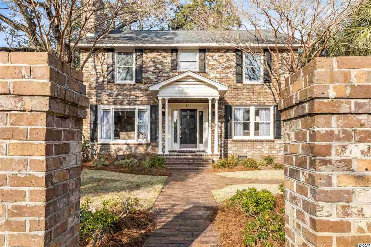 Enchanting, one-of-a-kind all-brick FULLY FURNISHED Charleston style home with a Carriage House nestled on the Avenues, just 240 yards from the beach! Main house offers 4 bedrooms and 3 bathrooms with two Master Suites, one first floor and a second upstairs. Carriage House offers separate living quarters of 2 bedrooms and 1.5 bathrooms. Boasting handsome hardwood flooring throughout and a cozy fireplace in the living room, the main home is a perfect blend of nostalgic charm and peaceful design. Delightfully open living/dining area creates a spacious, welcoming atmosphere, perfect for entertaining friends and family. Bright and cheerful kitchen offers convenient kitchen island Jennaire range and sleek black appliances. Breakfast room is filled with natural light by two picture windows and offers a counter with cabinet storage! Laundry Room offers Washer & Dryer, built-in ironing board, cabinets & shelving for storage! Floor plan offers first floor Master suite with full bathroom, as well as an upstairs Grand Master Suite with a huge, deep jetted soaking tub, separate shower, dual sink vanities and a ceiling fan.  Third and fourth bedrooms share a Jack & Jill bathroom. Spacious attic is floored, dry walled, offers 7' ceiling and two windows!  Just outside you will find a peaceful retreat offered by the covered back porch and mature landscaping, as well as enchanting brick walkways that weave through the beautiful mature landscaping and an outdoor shower with hot water, perfect for rinsing away the sand from a beach day!  The Carriage Home offers an open living/dining space on the first level, complete with a stove, sink, refrigerator and kitchen cabinets for ample storage, W/D hook-up and a half bath. The stairs lead up to two bedrooms and a full bathroom with tub/shower combination. Just outside, you will find a peaceful oasis in the courtyard, offering beautiful landscaping and peaceful fenced privacy. Outside storage areas built into the Carriage House! New irrigat