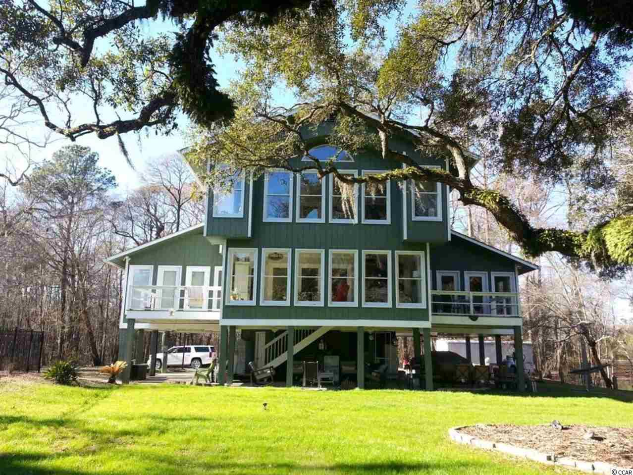 "**BUYER BONUS: CLOSING COST ASSISTANCE FOR USING PREFERRED ATTORNEY OR CASH BACK AT CLOSING!!**As you enter the property thru the stacked stone gated entrance, you're welcomed by this beautiful 3 BR (easily converted to a 4 or 5 BR), 4.5 BA river front home on the Waccamaw River with private canal and in-ground plaster pool. This home has it all - sitting on over an acre of land and situated under beautiful hardwood trees, including a magnificent 300+ year old Live Oak that is the focal point of the back yard, all in a very private location yet convenient to everything! Minutes from Downtown Conway, Carolina Forest (with the new International Drive connector open just a few miles away), close access to 501, 22 and 31, you cannot beat the privacy yet convenience to most areas! This custom home has an open layout with the entire rear consisting of glass doors and windows, along with decks off the dining area and Master BR, to capitalize on the beautiful setting. The completely remodeled interior (2014) boasts dark wide plank solid oak floors, custom staircase, custom lighting and ceiling fans, ceramic tile (kitchen, Carolina room, and 3 full baths), upgraded higher end stainless steel appliances (brand new gas cook top 2019), vaulted tongue and groove wood ceiling in upstairs bonus room, an exposed 3 story brick fireplace with custom mantle, and a huge bonus room upstairs that could be converted into an additional bedroom or two if needed. There's lots of storage inside and out, including clever hidden storage rooms accessed thru both upstairs bedroom closets. The concrete driveway has been expanded, creating lots of parking space for your ""toys"" or room for your guests coming to admire your new oasis. Brand new roof (2019) and new front steps (2019) with landing/side entry steps. This is the ultimate family home and is built for entertaining! The exterior living space boasts two floating docks on the river, a 220' lighted sea wall with stairs down to the canal for kayaking or swimming, a slide into the canal, rope swing into the river, and several sitting areas to enjoy the views. The in-ground pool is surrounded by brick pavers, and has a wet deck, therapy jets, slide and waterfall feature. The large side yard was recently fenced in if you have small children or pets. There is an outdoor kitchen area under the home with a built in fireplace/grill, sink area, and room for a fridge. Also underneath the home is an additional storage room with W/D hookups, a full bathroom, and an enclosed garage along with carport areas on both sides. Don't delay! Come see for yourself and make this your new luxury home on the water!"