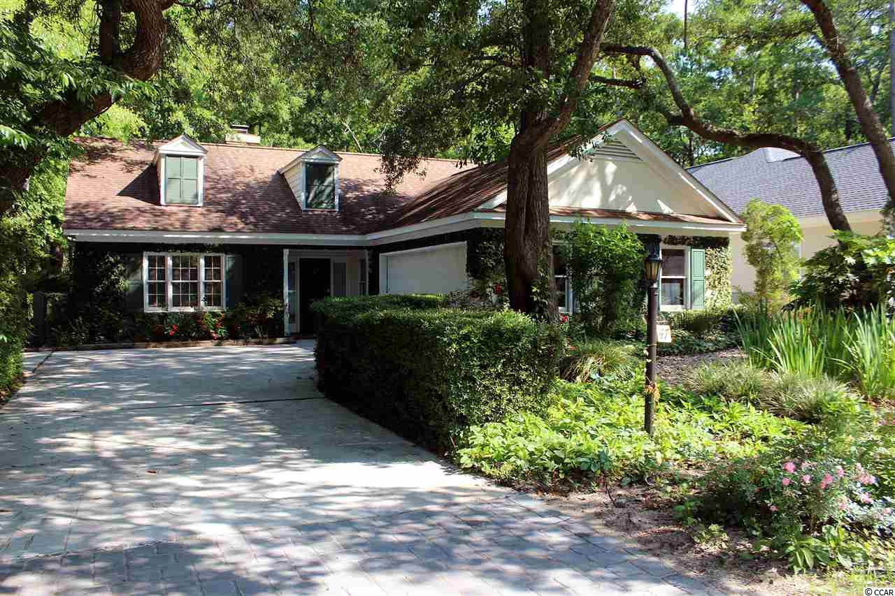 """Sellers have been the sole owners of this what neighbors refer to as the """"Charming European-Style one story classic home"""" located in a private setting with peeks of fairway #2 at Pawleys Plantation Jack Nicklaus Signature Golf course. The most beautiful aspect is the beautiful backyard, which features a secluded forest, viewed from the glassed-in (9 X 22) sun porch and out-door patio.  Enjoy back porch that overlooks a pond with soothing waterfall sounds, provides a relaxing oasis, which  sellers retire to almost daily. Three bedrooms, (one bedroom currently used for office), and two full baths. Master bath has a whirlpool tub, two sinks and a separate shower. Great room has a wood burning fireplace, wet bar, and vaulted ceiling. Large kitchen with eating area and lots of counter space.  Formal dining room and laundry room off of kitchen and a two car side loading garage.    Historic Charleston 65 miles south, Georgetown 10 miles south and Myrtle beach approximate 20 miles north.  Brookgreen Gardens and Huntington Beach State Park north in nearby Murrells Inlet.  Country Club and Golf Course Information Available upon request."""