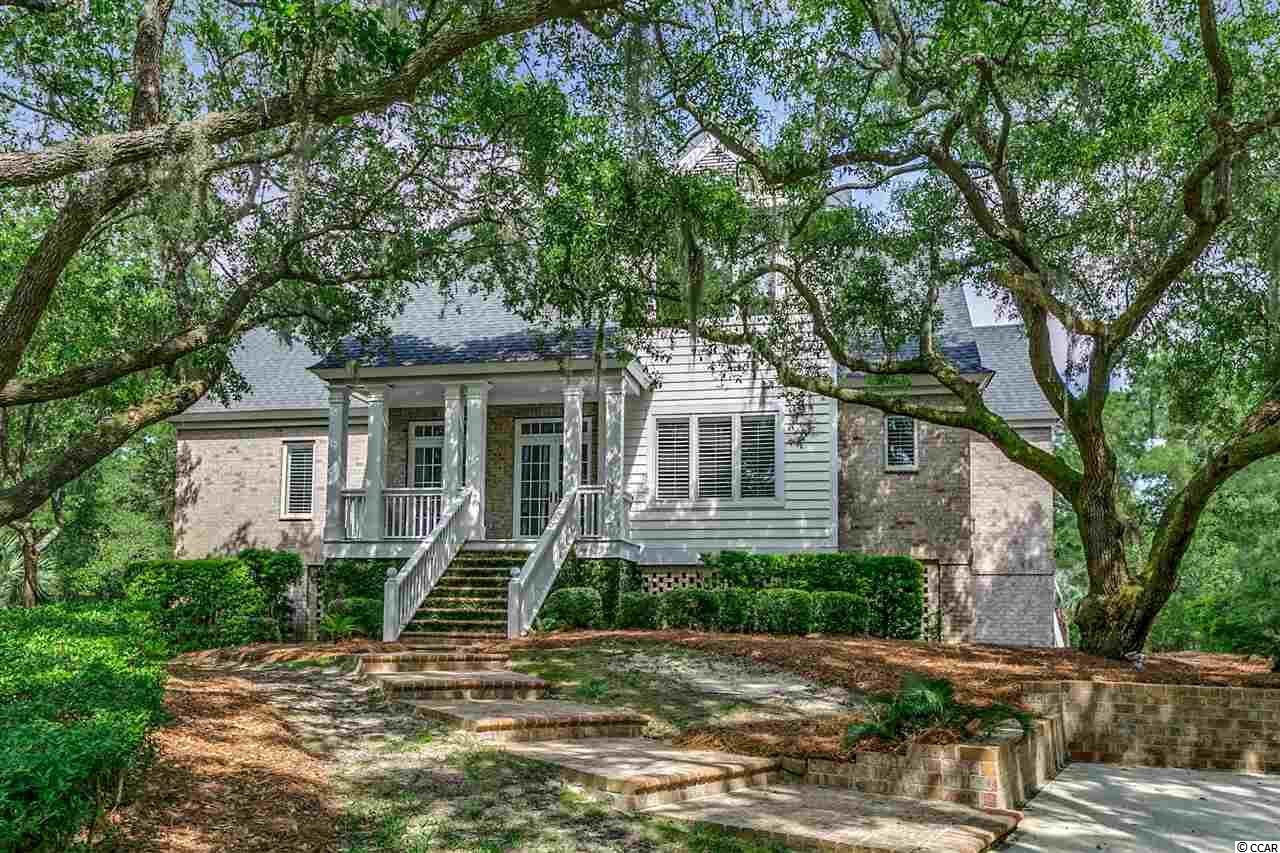 Beautiful coastal style home tucked away in the Island Community of DeBordieu Colony! This 4 BR 3.5 BA home offers a spacious floor plan, family room with fireplace and wet bar, kitchen with island, formal dining room and study,Carolina Room and deck overlooking the pond makes this home a great place to entertain with friends and family. Master bedroom and bath with large walk in closet are on the main floor. New roof in 2018. Just a short walk or golf cart ride to the beach!  DeBordieu Colony is a private gated oceanfront golf community located just south of Pawleys Island, SC. DeBordieu Colony Club is known for the 18 hole Pete Dye private golf course, ocean front dining at the Beach Club, tennis club and community pools. Private boat landing for those who enjoy fishing, kayaking or paddle boarding. Living in DeBordieu is like being on vacation everyday!