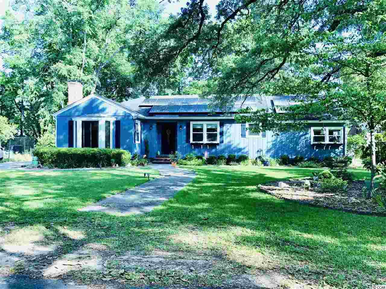 A rare recently FULLY RENOVATED home surrounded by live oak trees in the heart of Conway. Features SOLAR PANELS, new siding, kitchen, bathrooms, windows, sliding door, tankless water heater heated by gas, security system with cameras, and bay windows. This fully gutted and redone features a split bedroom plan offering you peace and quiet. As you walk in, you will find yourself in the foyer with a view of the living to your left and dining/open kitchen across you with a view of the screened porch behind dining room. Hardwood floors and newer paint running throughout the house with tile floors in bathrooms. Living room features 5 windows, including bay windows for plenty of sunlight overlooking the front yard. This modern open kitchen offers all new white cabinets, granite countertops and stainless steel appliances with windows overlooking the back yard. The two other bedrooms are overlooking the live oak tree in the front yard. If you are looking for SHADED WITH MANY TREES, LANDSCAPED WITH FLOWERS AND STONES BACK YARD, then this is the home for you. Motivated sellers, don't miss your chance to take a look at this house.