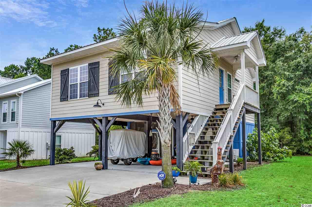 Welcome to your hidden gem located in the heart of Pawley's Island and just a short walk or 2 minute bike ride to the beach. This is the perfect 3 bedroom 2 bathroom raised beach house. This home features an open floor concept with vaulted ceilings and several upgrades including hardiplank siding, a metal roof, laminate throughout, and tile in bathrooms and laundry room. Kitchen has granite, newer stainless appliances, eat-in bar and a breakfast nook. Master bath has granite and a large soaking tub & shower. Guest bathroom also has granite. Outside the house is a large storage area and enjoy the private view sitting on your large enclosed patio. Great beach cottage or primary residence. This community features a pool for Pawley's Pointe residents only. This home won't last long, so call today to set up a showing.