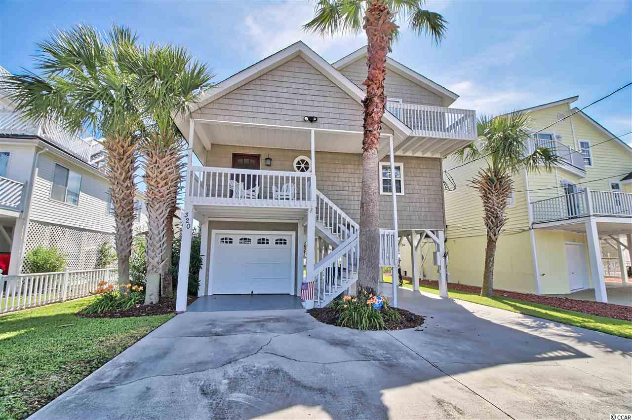Cherry Grove!  Absolutely gorgeous 4 bedroom, 2.5 bath raised beach house on the channel.  This home is a custom built home, unlike your normal shotgun style homes in Cherry Grove.  It features hardwood and tile floors, upgraded fixtures and ceiling fans, granite countertops in the kitchen and baths, stainless steel appliances, and decorated very nicely.  Outside, you have a one car garage with lots of storage, outdoor shower, balconies on all floors, and cedar shake vinyl siding. Located on a recently dredged channel, this home has a fixed dock, an aluminum gangplank leading down to a 15x20 floating dock.  New HVAC downstairs, new washer and dryer.  Golf cart is included in the sale!  Just steps or a short golf cart ride to the beach, or step out your back yard and explore/fish the Cherry Grove inlet in your boat or kayak.  This home has it all.