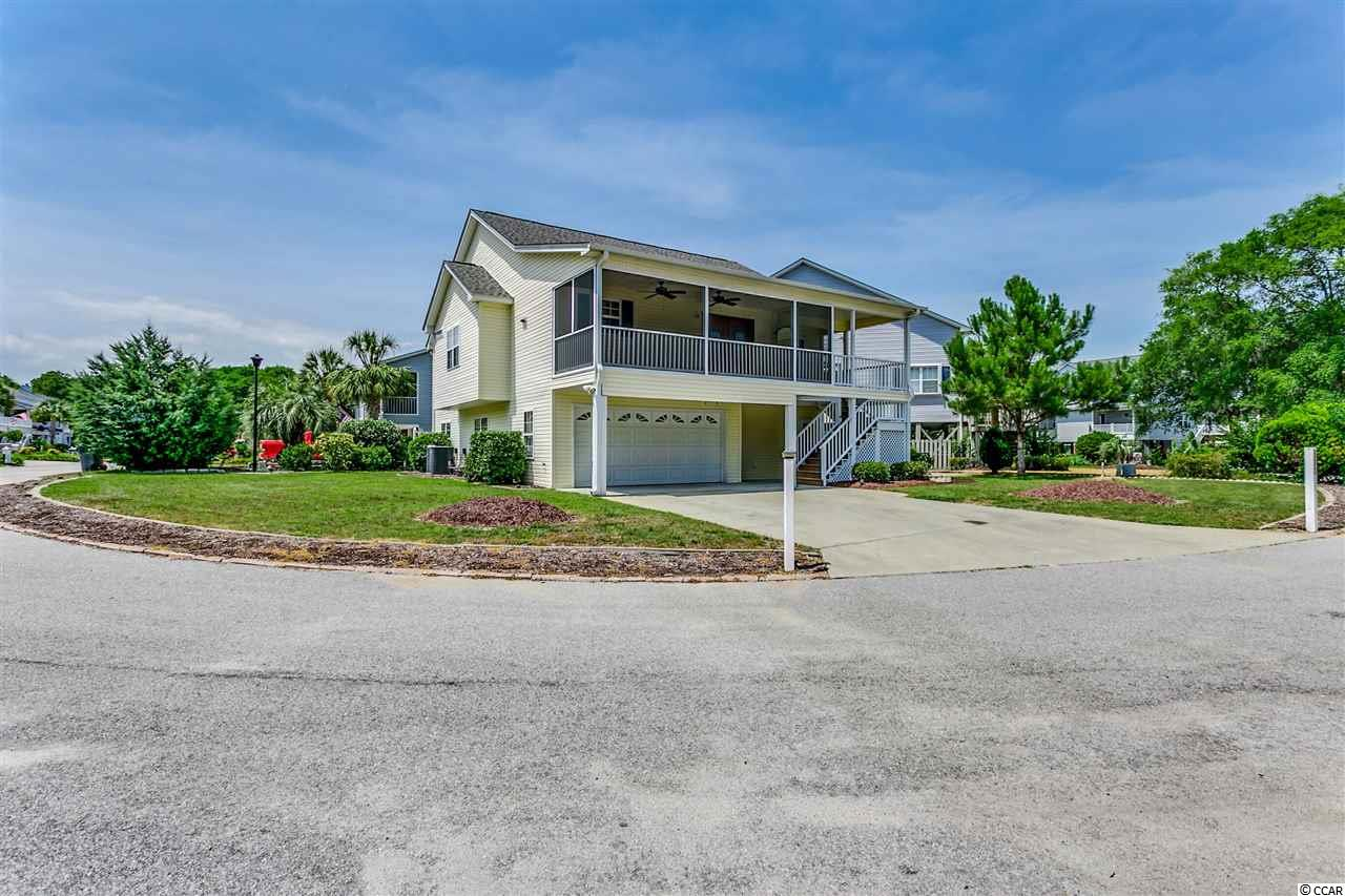 OPEN HOUSE:   SATURDAY, JULY 27TH 11:00 AM-1:00 PM.  Welcome Home!  4-bedroom, 3-bathroom raised beach house in the highly sought after Salters' Cove neighborhood.  Upstairs, you will find a large screened front porch -- perfect for relaxing in your rocking chairs and enjoying the breeze!  There is an expansive great room with a gas fireplace, an eating area, and full kitchen, along with three bedrooms, laundry area, and two full baths. The master suite features a walk-in closet, ceiling fan, whirlpool tub, double vanities, and a shower.  Downstairs (ground level) is a large mother-in-law suite, equipped with a kitchenette and full bathroom.  Area has a private entrance, plus there is an adjacent room, which can be completed to provide additional functionality and living space.  The attached garage will fit 4 cars, tandem style, or can be used for boats, toys, and other treasures.  There is even a workshop, off of the garage.  Have dogs? -- Kennel/dog run on the back of the home or use as a fenced-in garden. Salters' Cove offers a community pool, lake, tennis courts, playground, and clubhouse.  Great location so close to the beach, the Marshwalk, dining, shopping, medical, and all the entertainment Murrells Inlet has to offer.  Make this your primary residence, second home, or rental property.  Book your showing today!