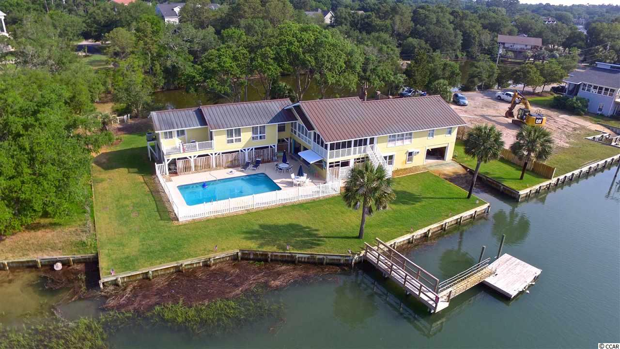 "This beautiful stately home is located on deep water in the heart of Murrells Inlet. Once you enter the private gates, you will be amazed by the privacy and  shear size of the lot. With 160 feet of creek frontage, this 4 bedroom 3 bath home gives you all the options that you need to be able to spread out! The North wing features two guest rooms and a full bath, all with amazing views of Murrells Inlet. The central part of the home has the kitchen, dining area, living room, and a serene screened porch; and guess what... they all have amazing creek views! The newest addition is the Southern Wing which features the Master suite, a private office, a private balcony, and a Master bath room that has views that will rival any bathroom in the world! The home features hand crafted real wood floors in the main living areas. The beautiful copper roof protects the home while also providing an beautiful look. Downstairs you will find the final bedroom, which is currently being used as the workout room, as well as a full bath and the laundry room. In the back yard, you will quickly learn that this home was built for entertaining. Whether you are hanging out on the couches, the bar, or summer kitchen area in ""Margaritaville""; dipping your toes in the large pool; or hopping on your boat for a sunset cruise; you and your friends will enjoy the tropical vibe of this creekfront home! The home also features a state of the art security system. Did I mention there is 160 feet of creek frontage and a private boat ramp? This home has it all. Call today for to set up a private tour."