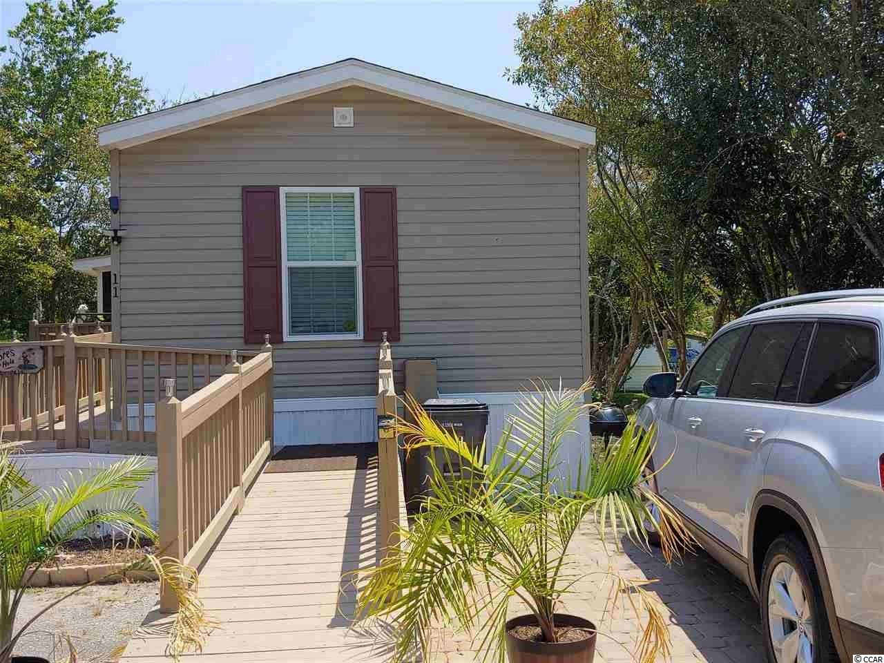 Like new 2017 Destiny single wide in the popular Garden City's Windjammer Village is now ready for your view. Only 1.3 miles from our beach, this 3 bed 2 bath gorgeous home features 8 foot ceilings and a large screened in porch at the entrance of the property.  A wheelchair ramp makes for easy accessibility to the porch and front door.  The shed on this property does convey for all of your storage needs and the gold cart inside is negotiable!  Your new beach home is already fenced in and has beautiful landscaping and mature trees.  Crown molding and chair rail are a few of the upgrades to this newer home. Come and enjoy this worry free home.  Move right in!  Vinyl plank flooring throughout!  It's beautiful.  Make it yours.