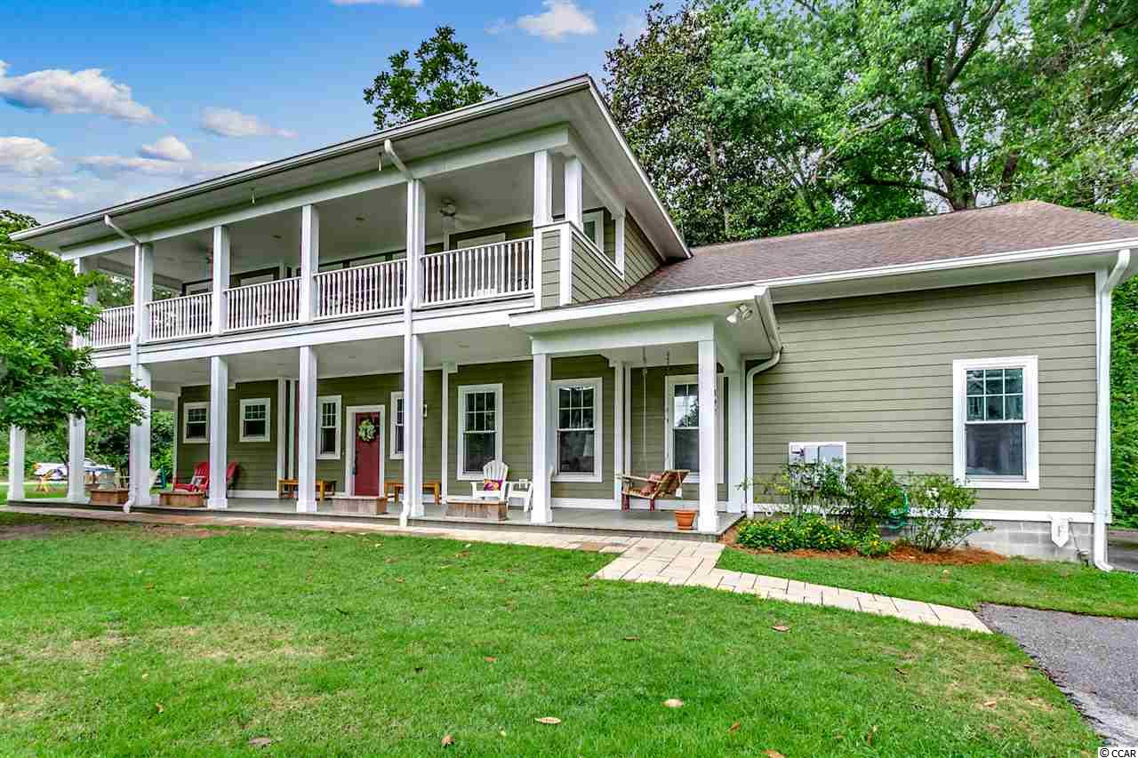 This Charleston style 5BR/3.5BA with views of Kingston Lake has the convenience of a new home among the historical section of downtown Conway. Enjoy quality time relaxing with friends and family on the spacious porch overlooking your wooded half-acre oasis. As you enter the grand foyer you'll be greeted with recessed lighting, engineered hardwood floors and crown molding throughout. Admire the attention to detail in hand picked custom upgrades at every turn. The formal dining room leads into a kitchen made for a chef with a farmhouse sink, stainless steel appliances, tile back splash, and trendy white cabinets.The kitchen looks out onto an impressive open living room with built ins and fireplace connecting to a newly added Carolina room giving you the perfect quiet place to relax and unwind. The spacious downstairs master bedroom is fit for royalty with a barn style door, huge sectioned closets, and en-suite bath with fully tiled walk-in rain forest shower and tub. As you make your way upstairs you're greeted by a cozy loft area buffering all the bedrooms. Bedrooms 3 and 4 share an outrageous exterior balcony providing the best view of Kingston Lake and an outstanding place to spend quality time. The 5th bedroom could be used as a large bonus room equipped with custom built in cabinets, and kitchenette. Heading back outside the large garage with oversized doors will accommodate boat and RV storage completing your slice of heaven tucked away in the middle of the city!  Square footage is approximate and not guaranteed.  Buyer is responsible for verification.