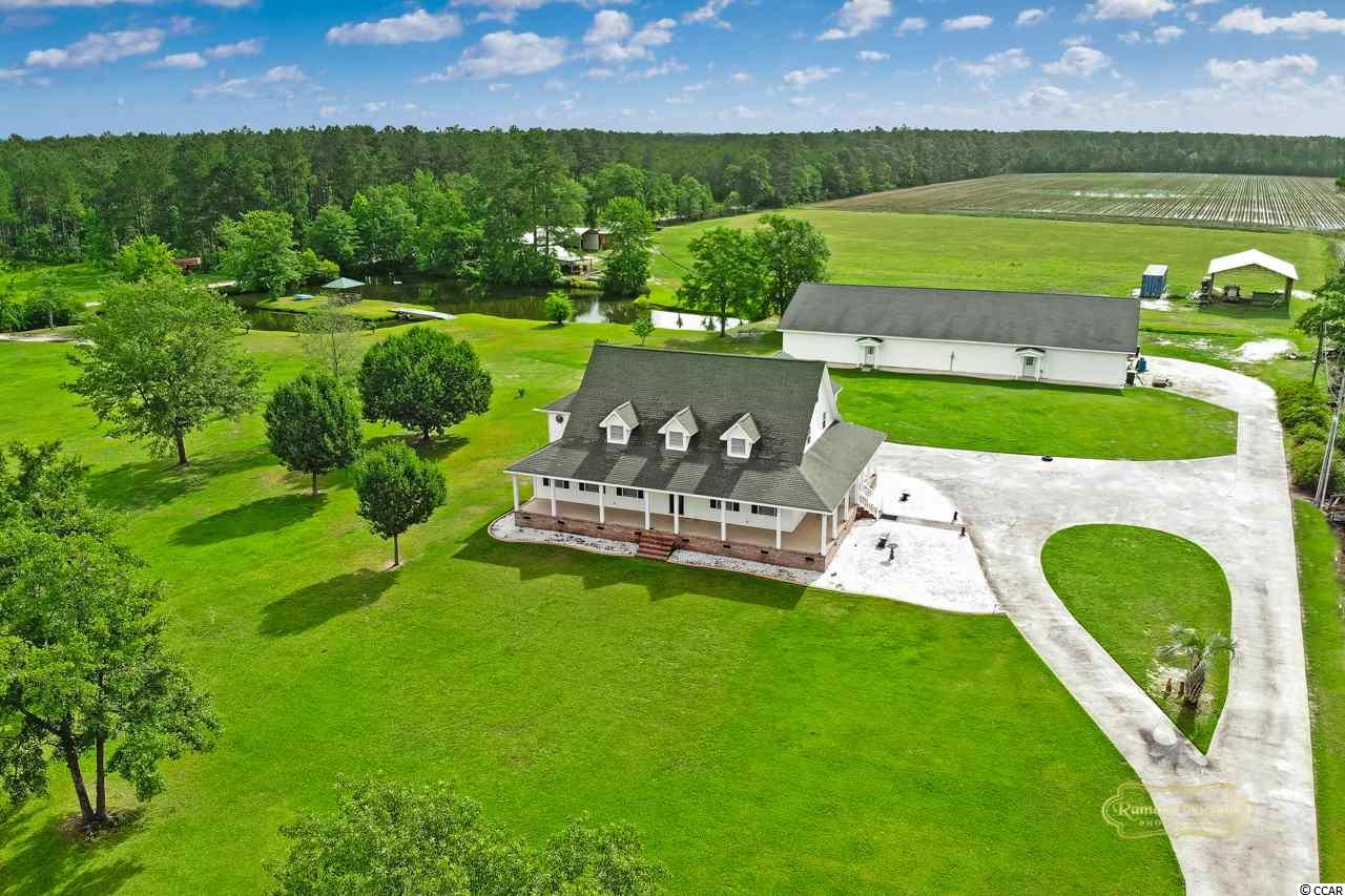 This is a must see property that offers multiple living spaces, workshops, storage, and acreage for the buyer who is looking for a one of a kind residence.  Beautiful custom built home with huge detached shop/garage with not 1 but 2 separate living quarters on 2+ acres of land. (additional land available) The main house has a lovely wrap around porch. The living area, kitchen, dining area, laundry room, den, 2 of the 4 bedrooms, and 1.5 baths are downstairs. The living areas have bamboo flooring. All appliances convey to include the washer/dryer. Upstairs, there's 2 more bedrooms and a full bath. The master suite is enormous with a sitting room, 2 closets in the bedroom, plus a 3rd (4 X 30 ft.) closet in the master bath. Master bath has double sink, whirlpool tub, shower, and laundry chute.  4th bedroom has 2 full size closets. There is unimproved attic space that could be finished for more living area. Furniture/furnishings in the main house are negotiable to include juke box. There's attached and detached storage rooms & a climate controlled office off of the carport. The  detached building is approximately 5000 sq. ft. It includes a newly renovated 3 room living quarters with full size kitchen appliances and a fireplace. A true and separate Mother in Law suite! There's a patio with beautiful pond and horse pasture views. Beyond a 3rd (though unfinished) living area, you'll find the shop/garage/farm building with open areas to work as well as rooms such as 10 X 10 saddle room. All appliances in the newly renovated apartment convey and furniture/furnishings are negotiable.