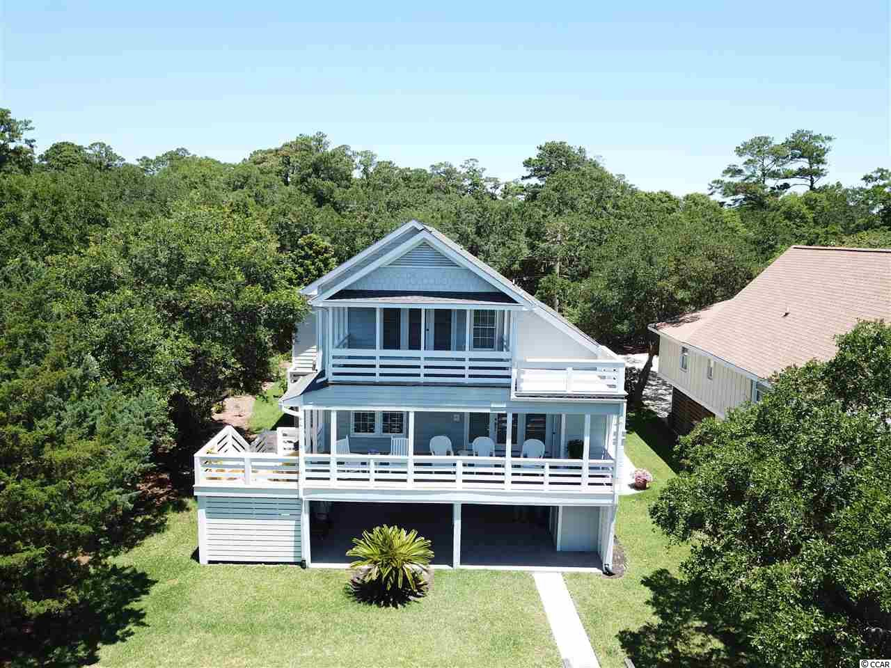 "What better address to call home other than 100 Comfort Lane! Breathtaking views across the Pawley Island Marsh, straight to the sand drenched Beach front at Pawleys point and the Atlantic Ocean. Trust me when I say this view will never get old! Sit on either of the two creek front decks and enjoy the almost constant breezes with your morning coffee or your afternoon beverage of choice. Better yet, walk out the upstairs bedroom and enjoy the beautiful sunrises, then try choosing between the main level porch, or the creek front dock for your afternoon gathering with friends and neighbors. For the sun worshipers you will enjoy the sun decks off both levels. This home is so unique in so many ways I really don't know where to start. All four bedrooms are essentially masters, boasting heated tile bathroom flooring, even the half bath. Three of the bedrooms have separate bathtubs and showers, with the fourth a tub / shower combo. All bedrooms and baths are very spacious with double sink vanities. For the men in the family each bedroom has large his and her closets! Attention to details show throughout this stately home, starting with the four locally produced stain glass masterpieces. Wainscoting, shiplap, and bead board throughout the structure with the front decks sporting haint blue bead board ceilings  Nice size laundry room and a house wide central vacuum. Large walk through storage area between the upstairs bedrooms with door entries from both sides. Another huge amenity is the three bay parking area that could easily park four or five cars and surrounds a 16'7""x15'5"" ground level workshop / man cave with a half bath and air conditioning. From the parking area there is a large motorized dumb waiter (equipped with a land line phone) capable of carrying a truck load of items to the main level deck. No words can describe this home properly so I encourage you to call today for a personal viewing, or ask your Real Estate professional to schedule a showing. You'll be impressed.  Please view the virtual tour at the top of the listing page for a more detailed rendering of the structure!"