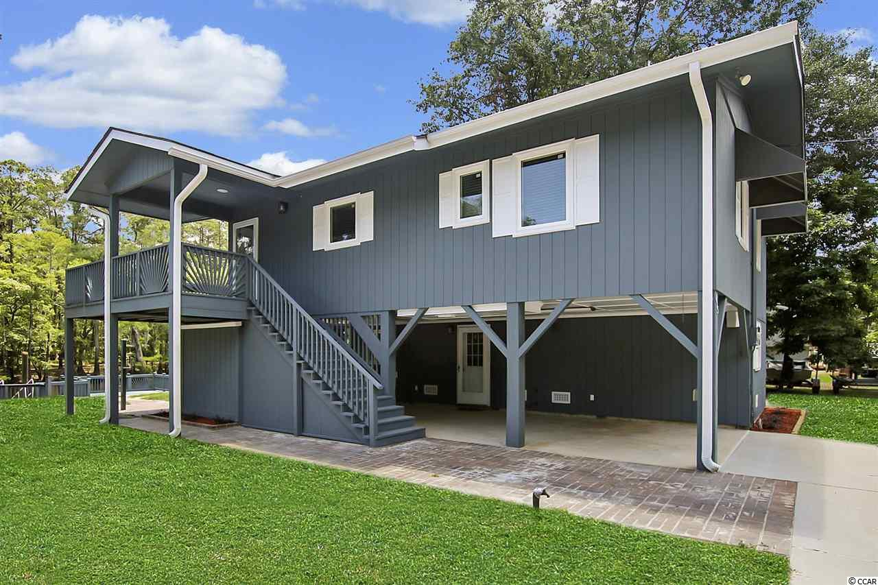 Presenting this sensational 2 bedroom 1 bath raised beach home located on the cypress lined & moss draped Waccamaw River. Bright and cheerful, this home is a nature lover's delight. Slowly maneuver your boat up to the 30 foot floating dock with 2 wings (10' X 10' and 10' X 12' approx), and completed with a full seawall & a bulkhead, modernized stationary river deck, and a fish cleaning station. This home offers beautiful hardwood & tile flooring, crown moulding, spacious main living area encompasses a delightfully open living/dining floor plan with fully equipped kitchen with side by side stainless steel refrigerator with ice and water door dispenser, and ample counter & cabinet space. Large glass sliding door leads out to your sun drenched balcony and the perfect spot to enjoy an early morning cup of coffee over looking the Waccamaw River. The spacious bedrooms come complete with ceiling fans and walk-in closets. The bathroom updated with new vanity & toilet and finished with a walk-in shower. The ground level could be finished as an in-law suite or guest quarters. This home provides you close proximity to the beach and golfing along with all the other attractions and amenities of Myrtle Beach and a short boat ride to Conway, with fine dining, wonderful world-class entertainment, fishing piers, exciting shopping experiences on the Grand Strand, Conway's antique shops, and the River Walk. Just a short drive to medical centers, doctors' offices, pharmacies, banks, post offices, and grocery stores. Check out our state of the art 4-D Virtual Tour.