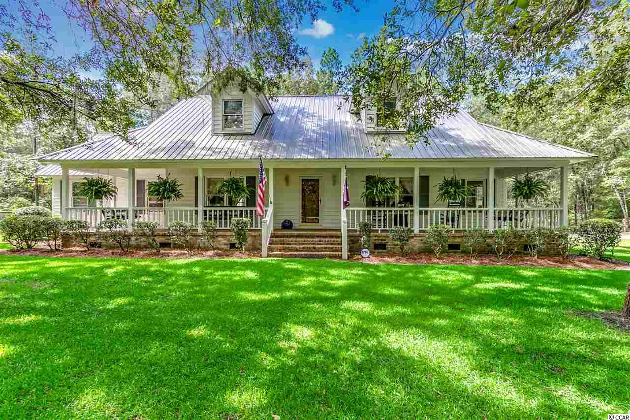 If you're looking for a little peace and quiet, look no further than this beautiful low country style home just minutes from Conway and off the beaten path near Bucksport Marina. This charming 3 bedroom home exudes seclusion, privacy and plenty of space on nearly 2 acres of land! Outside, you'll immediately notice the natural landscape, providing lots of shade to cover the home, large boat shed and a three-bay lean-to. Venture to the large, near wraparound front porch and you'll fall in love in love with the brick under your feet and beautiful porch swings on either side offering the perfect spot to read a book while listing to the birds sing their morning songs. Inside the home, you'll be pleasantly surprised at the vast storage space almost everywhere you turn. The builder was sure to utilize every space possible for an additional linen closet, storage closet, or attic access.  You'll find that many closets have another storage closet in them!  The kitchen has an updated refrigerator, oven and dishwasher as well as a gas stove, walk-in pantry and plenty of cabinet space.  The open living room with gas fireplace is the perfect setting for family get-togethers and features built-in cabinets to display all your books and knickknacks.  Located directly off the living room, the master bedroom has a nice sized walk-in closet, linen closet and connected master bathroom.  The other two bedrooms are upstairs, have two closets each and feature a skylight in each room.  At the bottom of the stairs and off the living room, you'll find a wonderful screened-in back porch perfect for enjoying those warm, southern summers.  Ready to view your new home boasting peaceful privacy?  Call today to schedule an appointment!